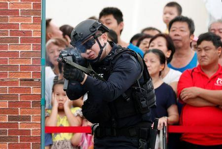 Police take part in a simulated gunmen attack demonstration for the public at a housing estate in Singapore