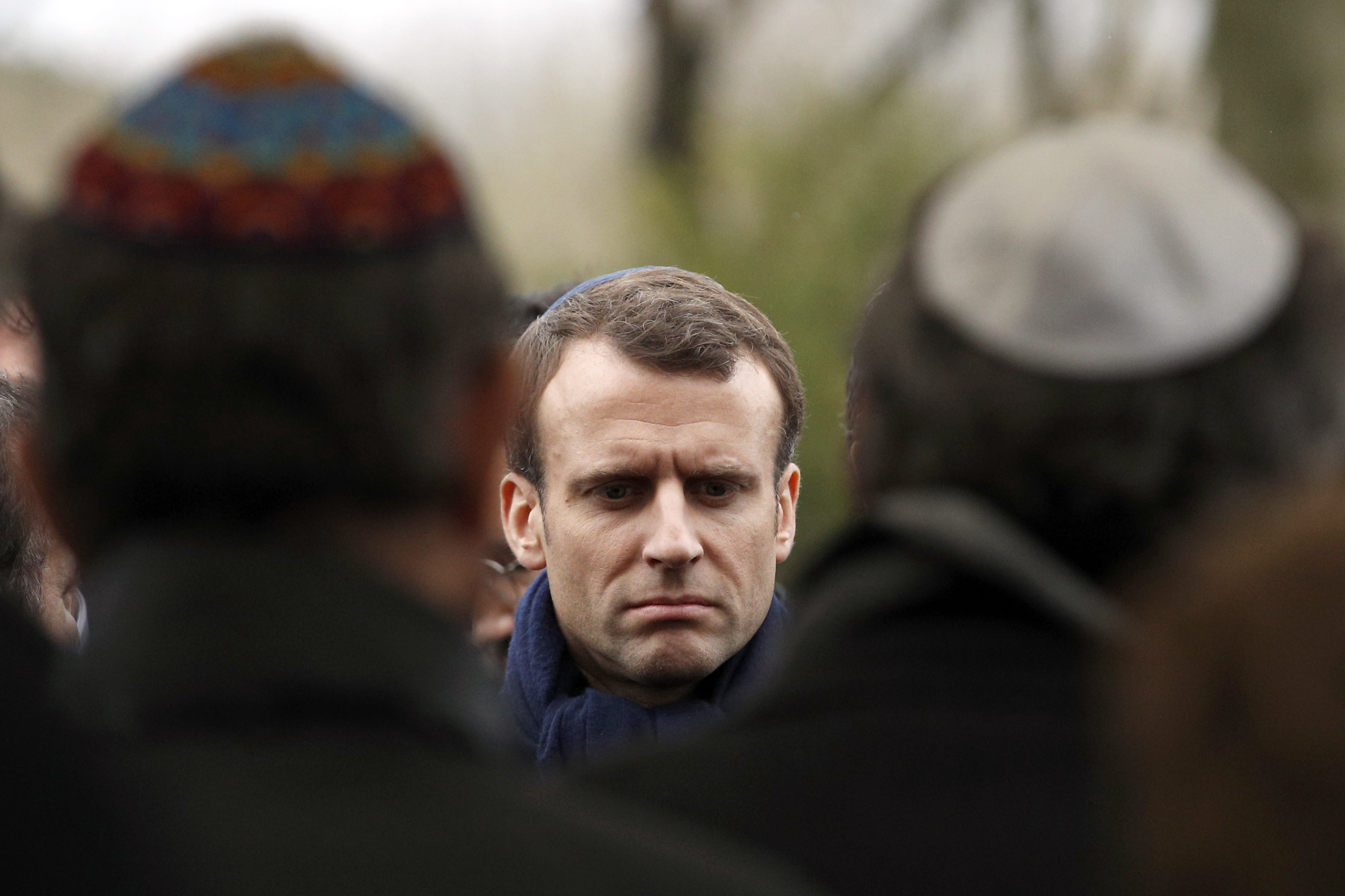FILE - In this Wednesday, March 28, 2018 file picture French President Emmanuel Macron attends Mireille Knoll's funerals at the Bagneux cemetery , outside Paris. Family members and friends gathered Wednesday to honor an 85-year-old woman who escaped the Nazis 76 years ago but was stabbed to death last week in her Paris apartment, apparently because she was Jewish. France's prime minister is sounding the alarm over a sharp rise in anti-Semitic acts this year, pledging to increase efforts to punish perpetrators and police hate speech online. (AP Photo/Christophe Ena, File)