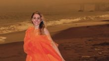 Influencer catches flak for posing in a vibrant orange dress, amid eerily glowing sky, during California fires