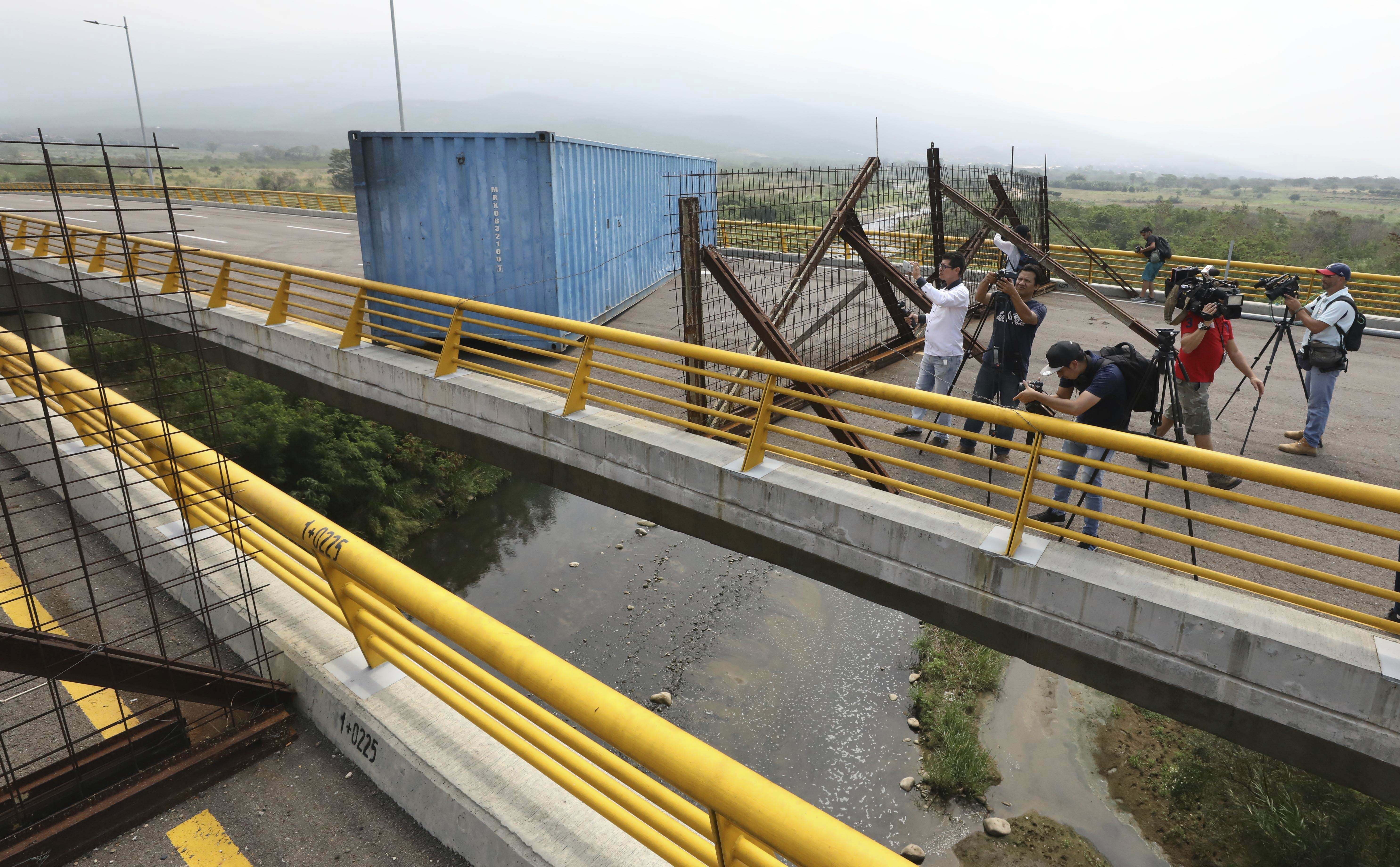 Journalists record a fuel tanker, cargo trailers and makeshift fencing, used as barricades by Venezuelan authorities attempting to block humanitarian aid entering from Colombia on the Tienditas International Bridge that links the two countries as seen from the outskirts of Cucuta, Colombia, Wednesday, Feb. 6, 2019. Immigration authorities say the Venezuelan National Guard built the roadblock a day earlier. (AP Photo/Fernando Vergara)