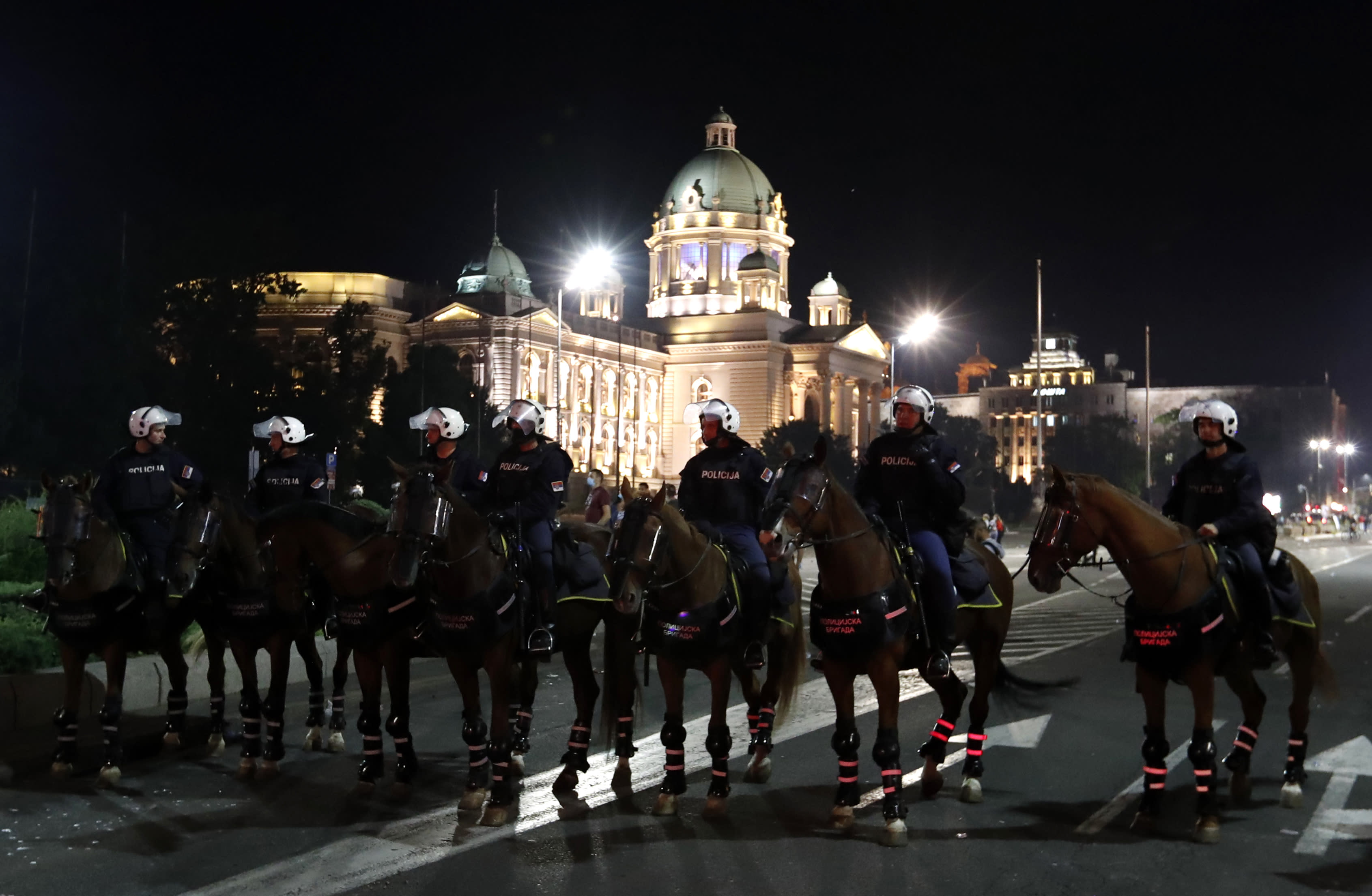 Serbian police guards the area in front of the parliament building after clashing with protesters in Belgrade, Serbia, Wednesday, July 8, 2020. Police have fired tear gas at protesters in Serbia's capital during the second day of demonstrations against the president's handling of the country's coronavirus outbreak. President Aleksandar Vucic backtracked on his plans to reinstate a coronavirus lockdown in Belgrade this week, but it didn't stop people from firing flares and throwing stones while trying to storm the downtown parliament building. (AP Photo/Darko Vojinovic)
