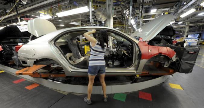 GM auto worker Martinez installs parts on a car at GM's Fairfax plant in Kansas City Kansas