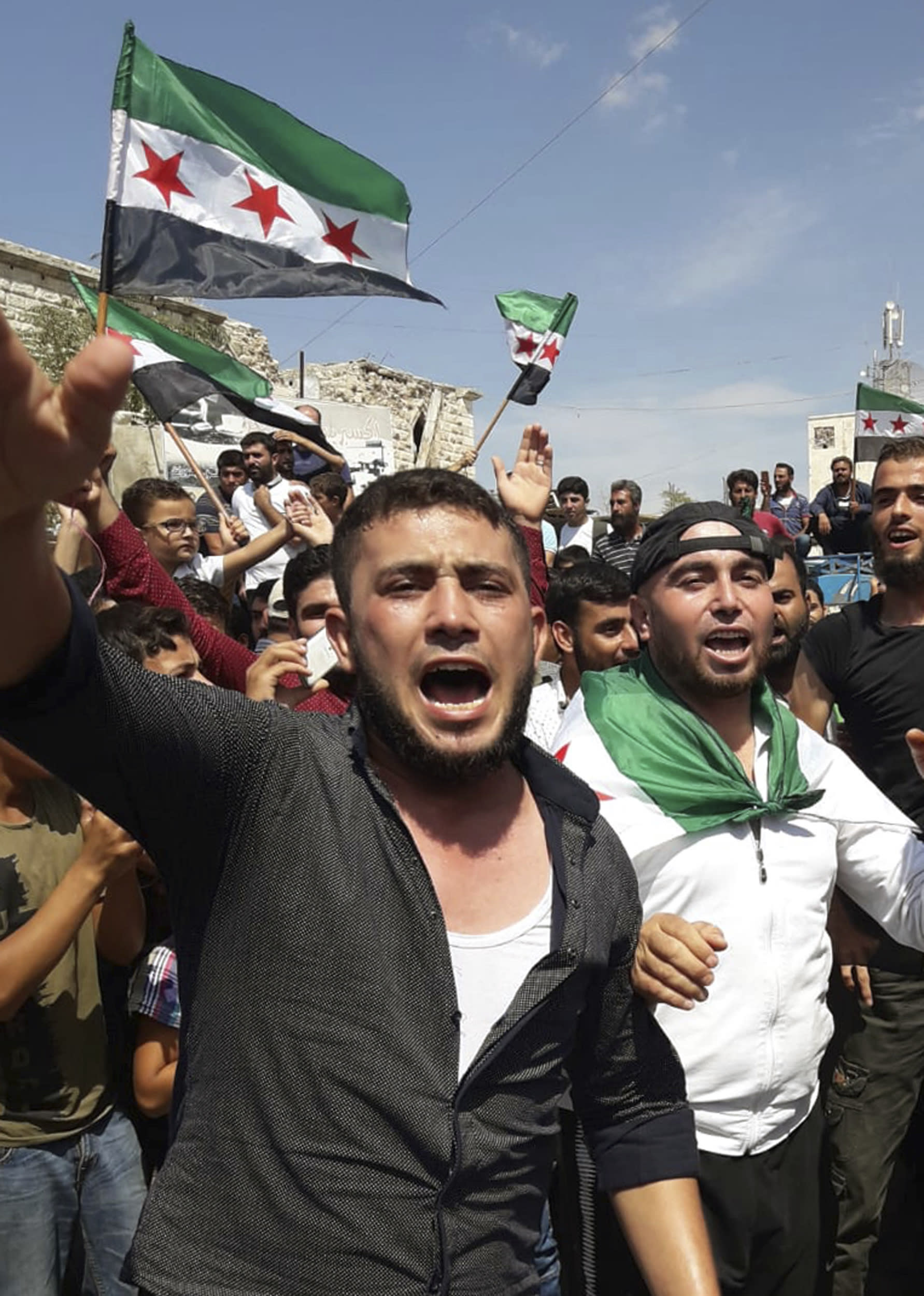This image courtesy of Mustafa Alabdullah, an activist and resident of Idlib, shows protesters chanting as they holding Syrian revolution flags, in Harim, a town in Idlib province, Syria, Friday, Sept 7, 2018. The rallies were a day of protests against Syrian President Bashar Assad and his troops' imminent offensive against Idlib, the last bastion of rebels in Syria. The Friday rallies came as Presidents of Iran, Turkey and Russia are meeting in Tehran to discuss the war in Syria. The summit may determine whether diplomacy halts any military action in Idlib and its surrounding areas, home to more than 3 million people. Nearly half of the area's residents are already displaced from other parts of Syria and have refused to reconcile with the Syrian government. (Courtesy of Mustafa Alabdullah via AP)