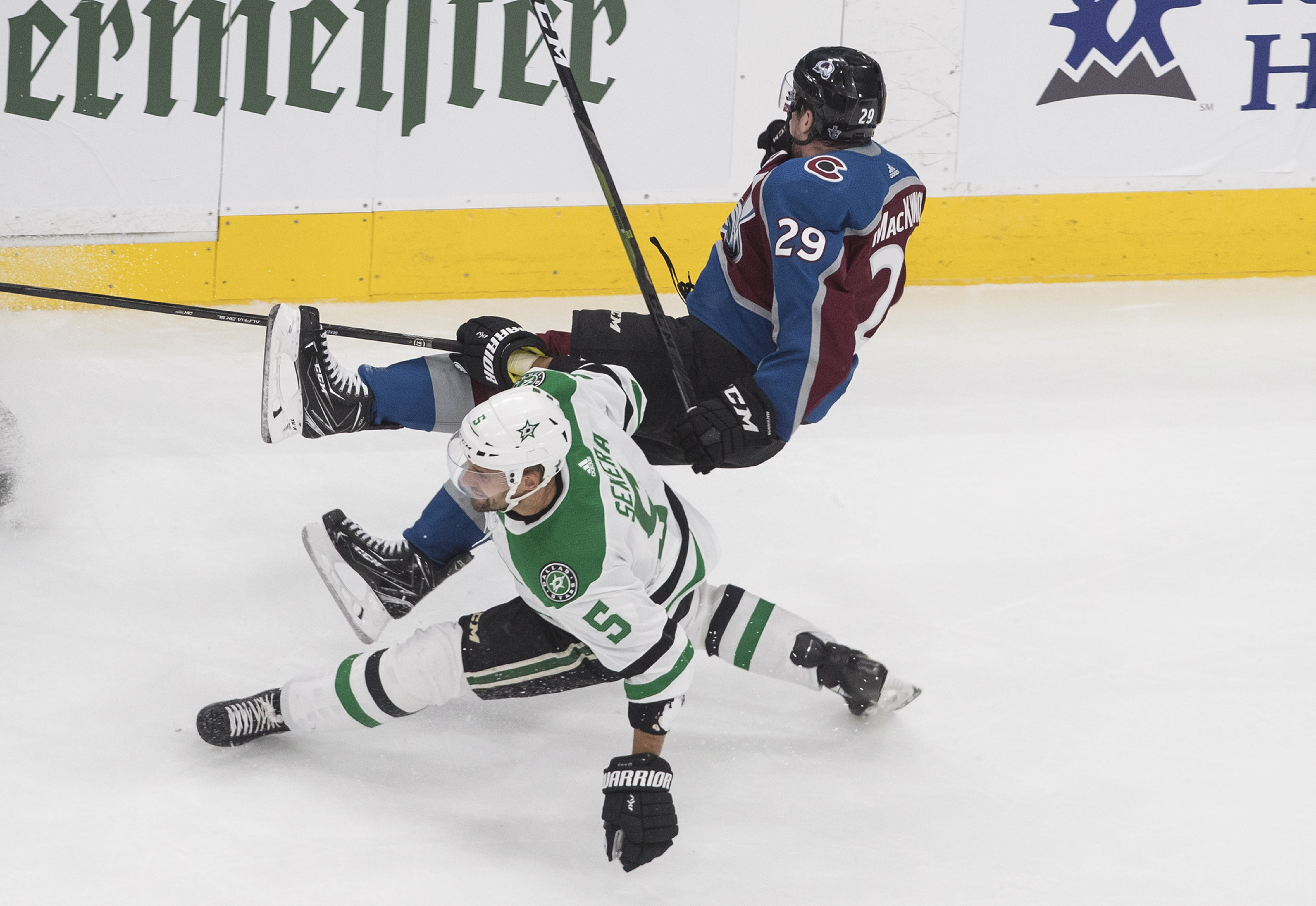 Colorado Avalanche center Nathan MacKinnon (29) is checked by Dallas Stars defenseman Andrej Sekera (5) during third-period NHL Western Conference Stanley Cup playoff hockey game action in Edmonton, Alberta, Saturday, Aug. 22, 2020. (Jason Franson/The Canadian Press via AP)