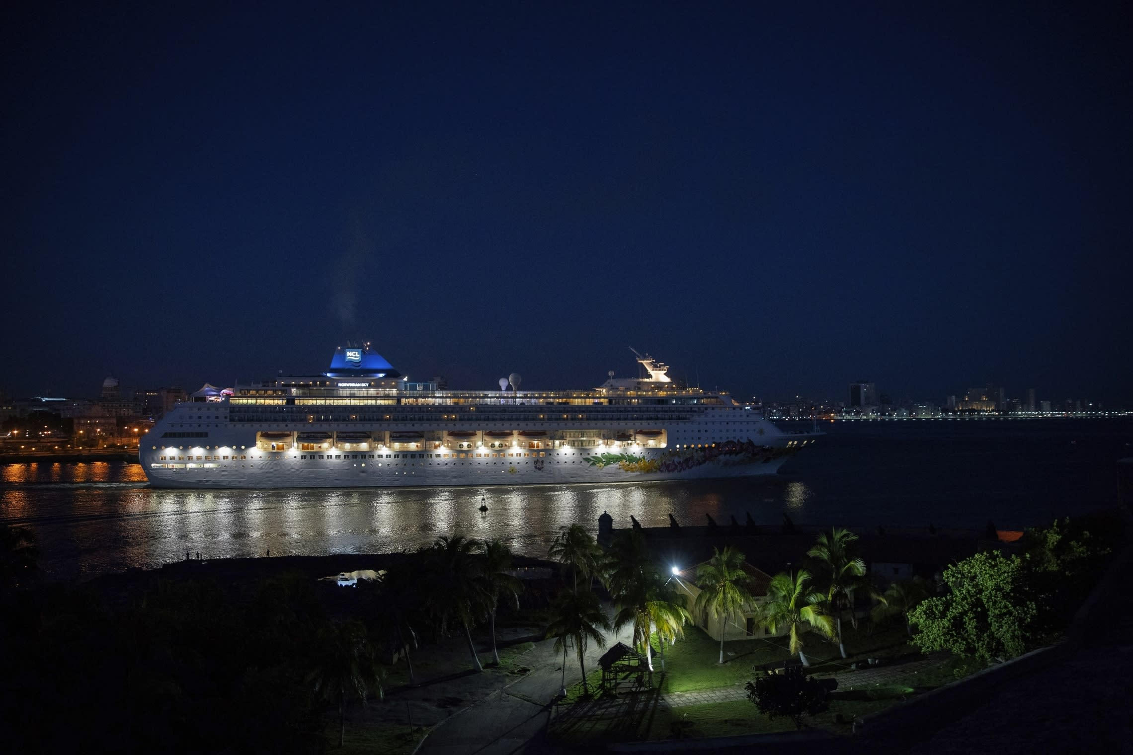 A ship of the Norwegian Cruise Line leaves the bay of Havana at dawn, in Havana, Cuba, Wednesday, June 5, 2019. The Trump administration has imposed major new travel restrictions on visits to Cuba by U.S. citizens, banning stops by cruise ships and ending a heavily used form of educational travel as it seeks to further isolate the communist government. (AP Photo/Ramon Espinosa)