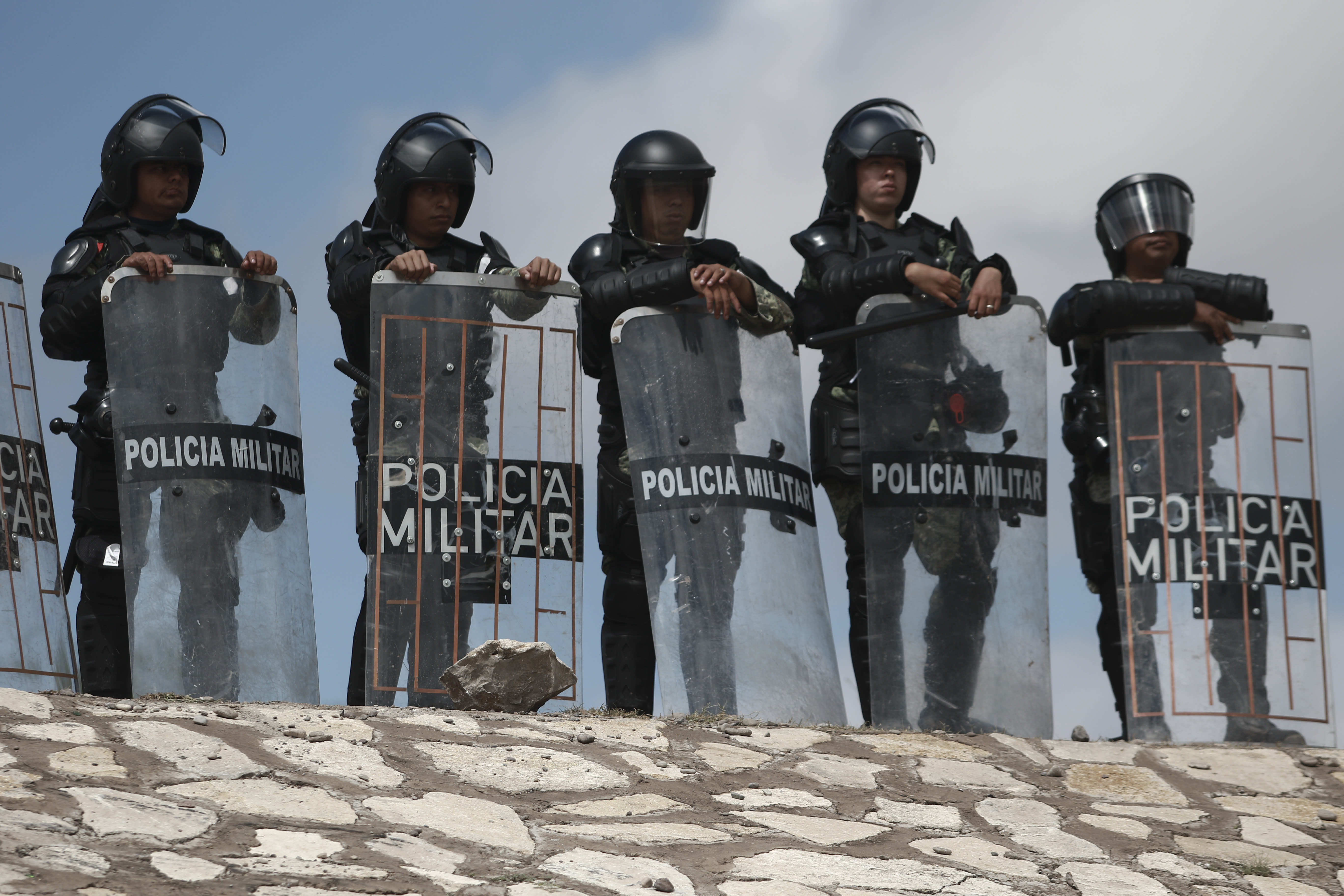 National Guard troops equipped with riot gear stand guard at Las Pilas dam, two days after withdrawing from the nearby Boquilla dam after clashing with hundreds of farmers, in Camargo, Chihuahua State, Mexico, Thursday, Sept. 10, 2020. President Andrés Manuel López Obrador said Thursday he regretted the killing of a woman and the wounding of her husband following a Tuesday clash between National Guard troops and farmers over water. (AP Photo Christian Chavez)