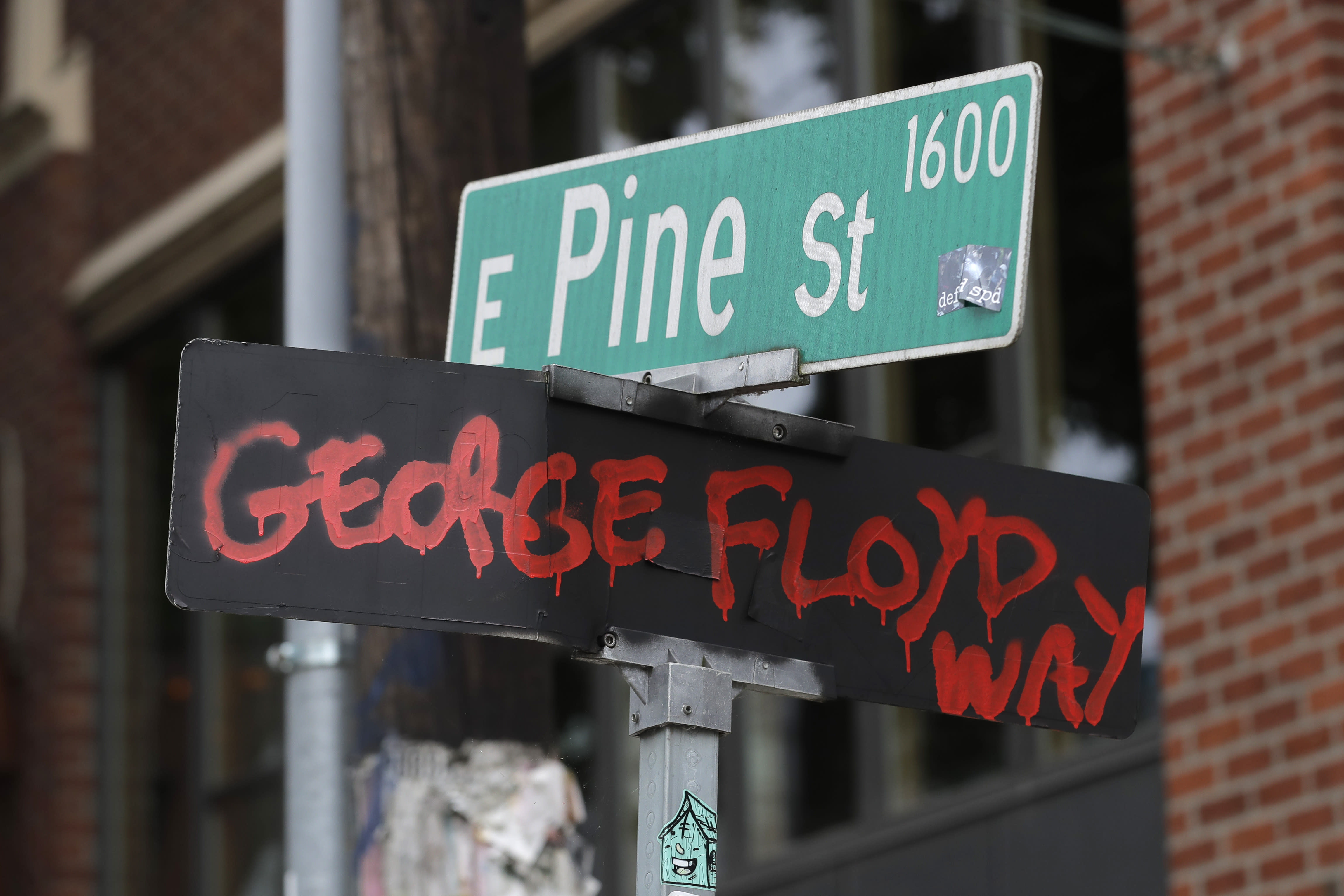 "A street sign at the intersection of 11th Ave. and Pine St. has been changed to read ""George Floyd Way,"" Wednesday, June 24, 2020, inside the CHOP (Capitol Hill Occupied Protest) zone in Seattle. The area has been occupied since a police station was largely abandoned after clashes with protesters, but Seattle Mayor Jenny Durkan said Monday that the city would move to wind down the protest zone following several nearby shootings and other incidents that have distracted from changes sought by peaceful protesters opposing racial inequity and police brutality. (AP Photo/Ted S. Warren)"