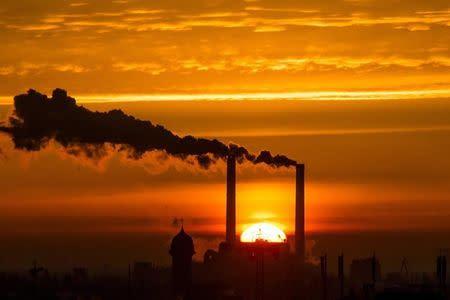 Sun rises behind billowing chimneys of power station in Berlin