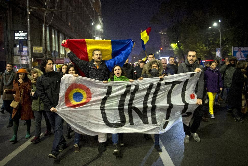 """People demonstrate with a banner reading """"United"""" in a street of Bucharest, to protest against Romanian Prime Minister and presidential candidate Victor Ponta on November 8, 2014"""