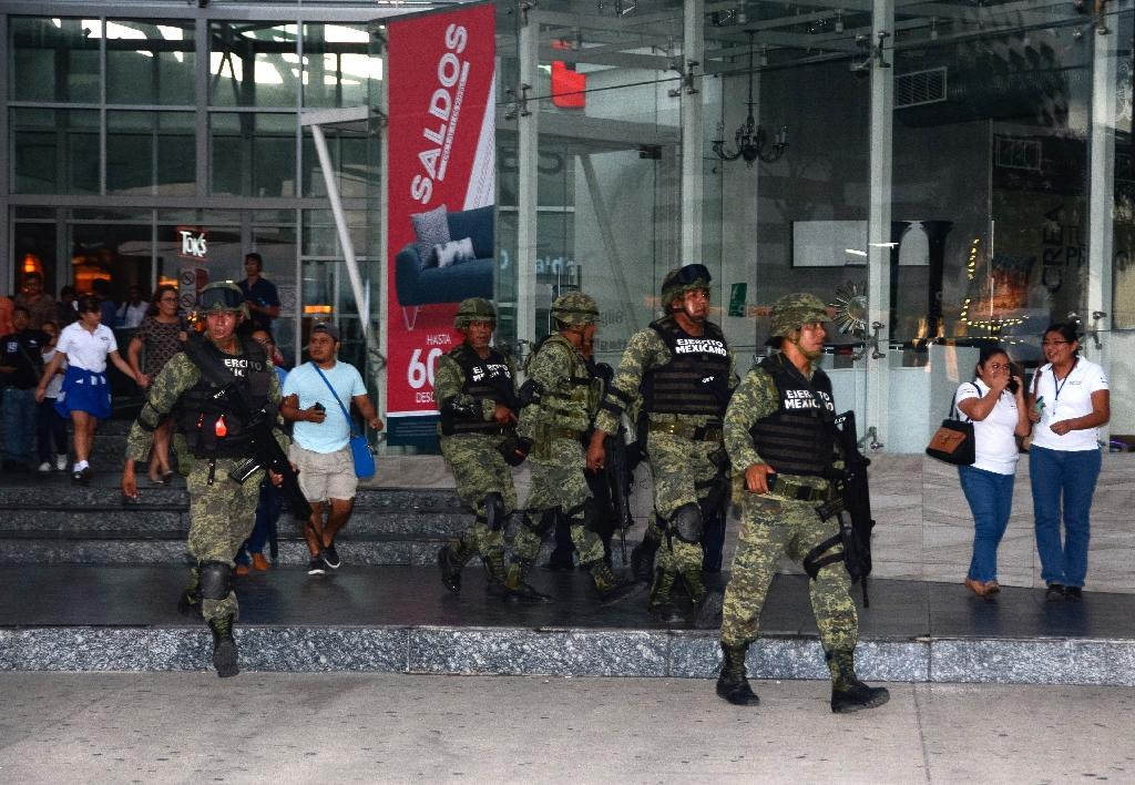 Soldiers evacuate civilians from a shopping center near Quintana Roo state prosecutor's office in Cancun, Mexico, during a shootout at the office which left four dead (AFP Photo/)