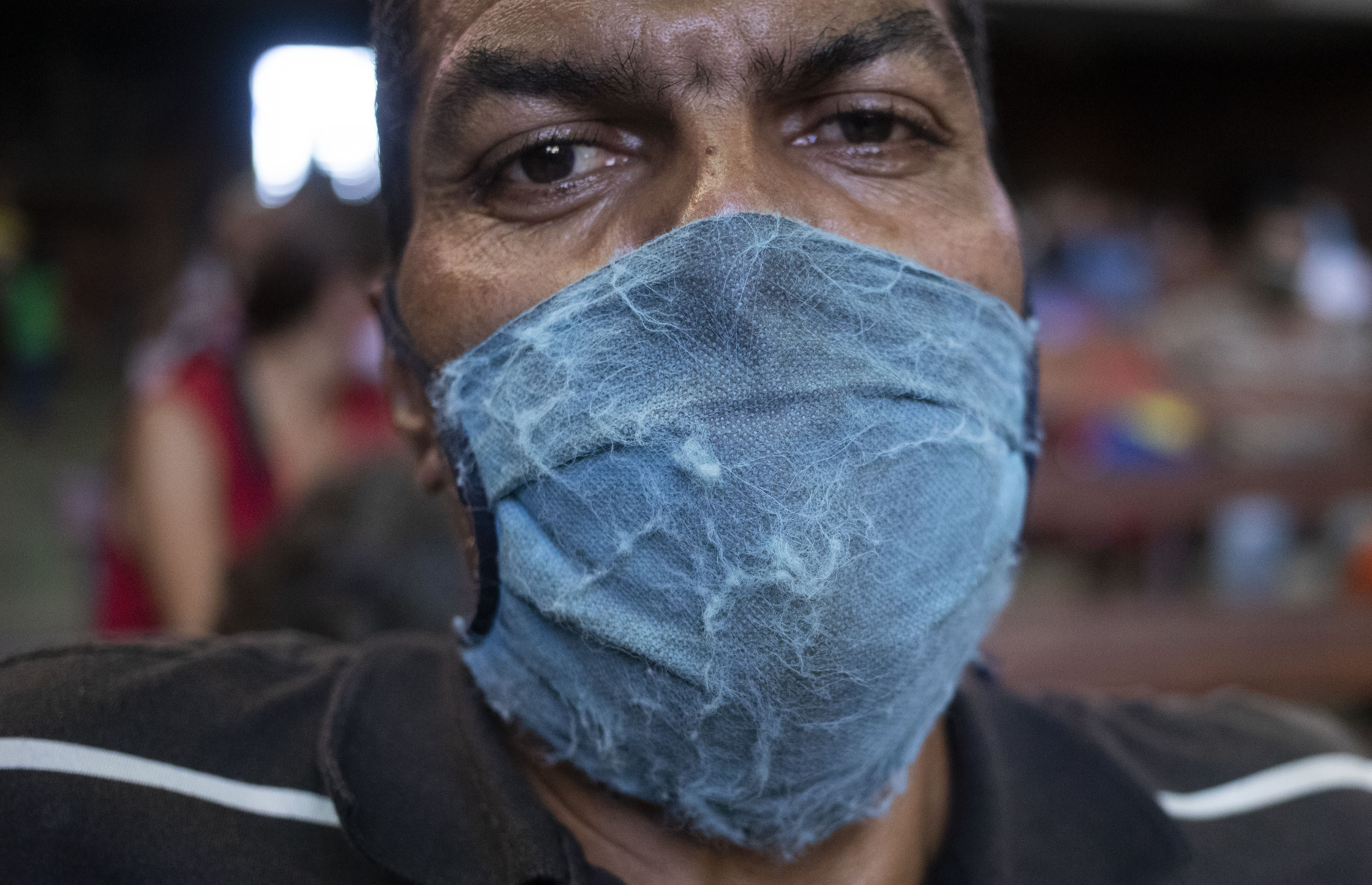 A man, wearing a weathered protective face mask as a precaution against the spread of the new coronavirus, waits to receive a free meal at a church in The Cemetery neighborhood of Caracas, Venezuela, Friday, May 22, 2020. The number of people who come looking for food at the church has increased in quarantine. (AP Photo/Ariana Cubillos)