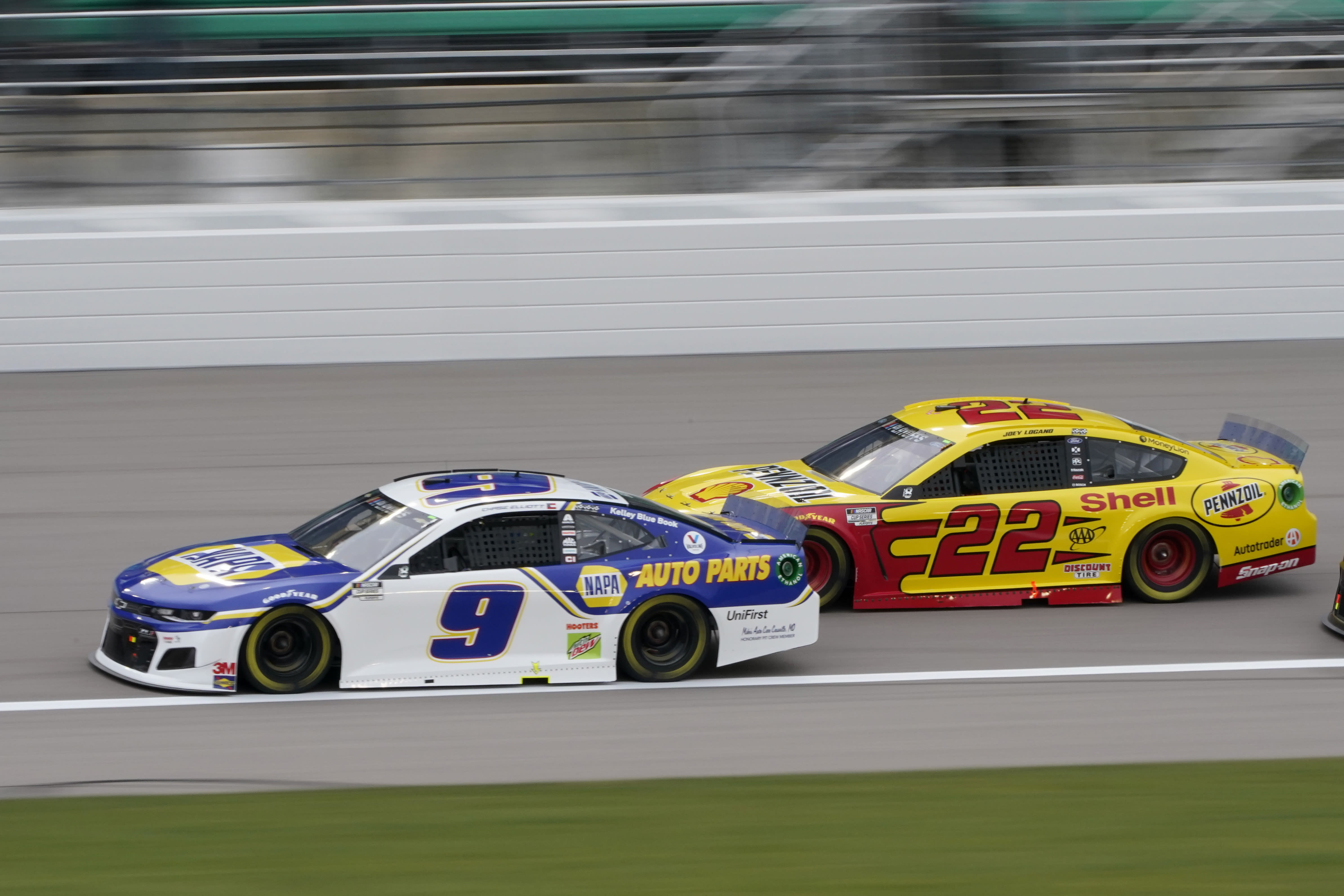 Chase Elliott (9) leads Joey Logano (22) on the first lap of a NASCAR Cup Series auto race at Kansas Speedway in Kansas City, Kan., Sunday, Oct. 18, 2020. (AP Photo/Orlin Wagner)