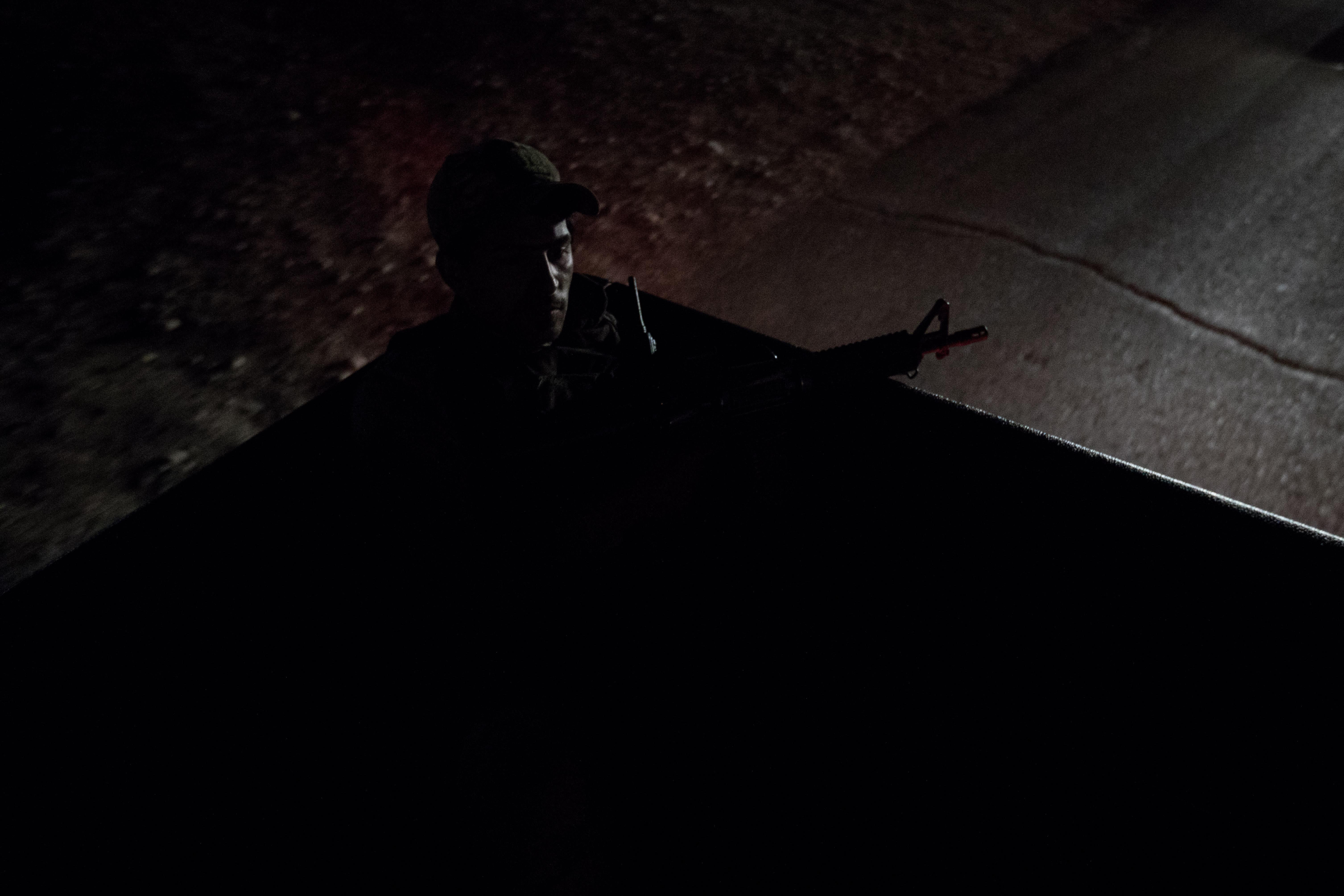 <p><b><em>Baiji, Iraq</em>   </b> A Shia militia Hashd al-Shaabi fighter rides on the back of a pickup truck heading towards a nighttime operation targeting the terrorist militia Islamic State group, which hides in this region. (Photo: Sebastian Backhaus) </p>