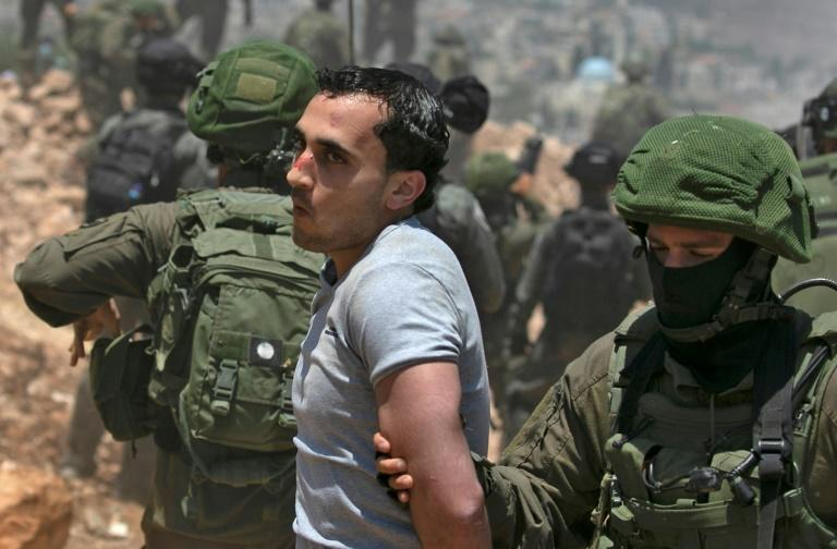 Israeli forces detain a Palestinian demonstrator amid clashes during a protest against Jewish settlements and Israel's planned annexation near the West Bank city of Nablus on July 10 (AFP Photo/ABBAS MOMANI)