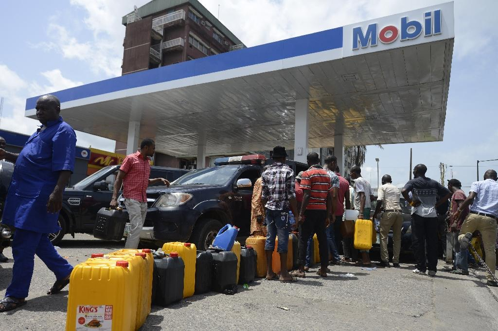 People queue with jerrycans to buy fuel at Mobil filling station in Lagos on May 21, 2015 (AFP Photo/Pius Utomi Ekpei)