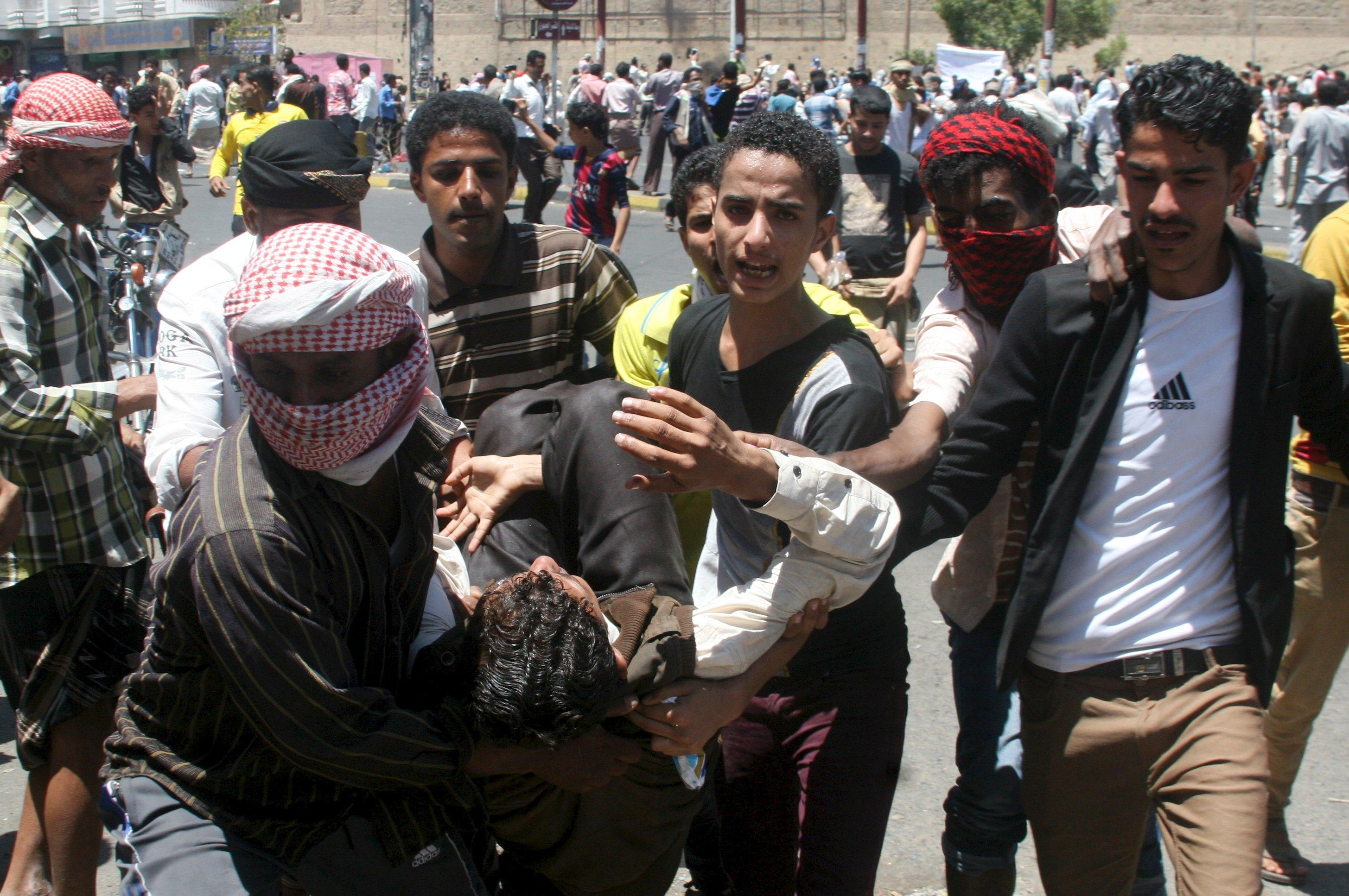 Anti-Houthi protesters carry an injured fellow protester during clashes with Houthi fighters in Yemen's southwestern city of Taiz March 22, 2015. Houthi fighters opposed to Yemen's president took over the central city of Taiz in an escalation of a power struggle diplomats say risks drawing in neighboring oil giant Saudi Arabia and its main regional rival Iran. Residents of Taiz, on a main road from the capital Sanaa to the country's second city of Aden, said that Houthi militias took over the city's military airport without a struggle from local authorities late on Saturday. REUTERS/Anees Mahyoub