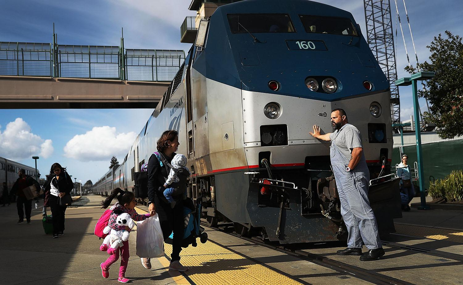 <p>An Amtrak engineer leans on the locomotive as passengers disembark from Amtrak's California Zephyr at the end of its daily 2,438-mile trip to Emeryville/San Francisco from Chicago, which took roughly 52 hours, March 25, 2017, in Emeryville, Calif. President Trump has proposed a national budget that would terminate federal support for Amtrak's long distance train services, which would affect the California Zephyr and other long-distance rail lines run by Amtrak. (Photo: Joe Raedle/Getty Images) </p>