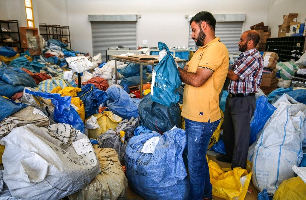 Palestinian postal workers go through sacks of previously undelivered mail, blocked by Israel from entering the West Bank for up to eight years, in the city of Jericho on August 14, 2018