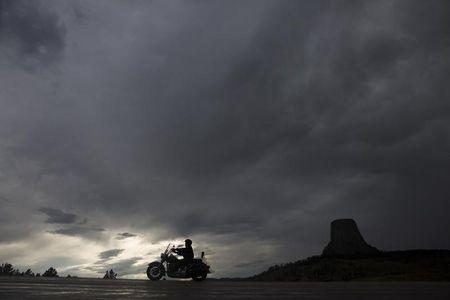 A motorcyclist cruises past Devils Tower National Monument