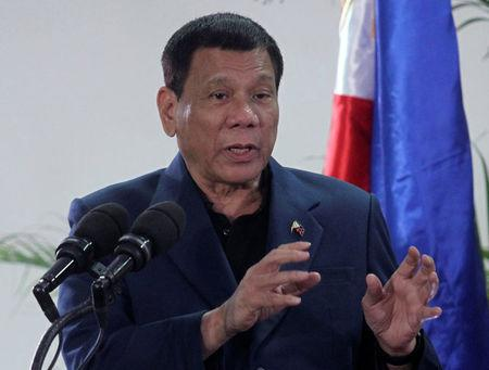 Philippine President Rodrigo Duterte interacts with reporters during a news conference upon his arrival from a four-day state visit in China at the Davao International Airport in Davao city
