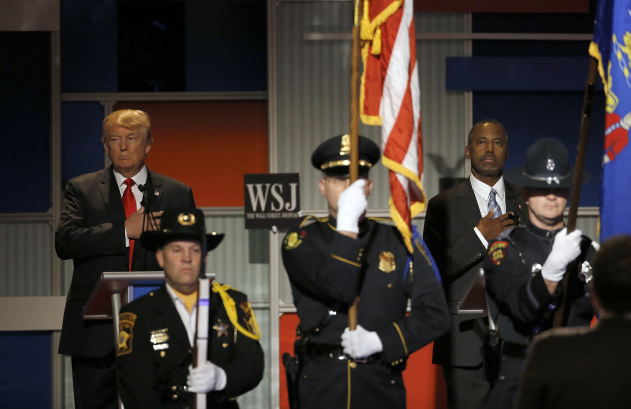 <p>Donald Trump, left, and Ben Carson salute during the national anthem before Republican presidential debate at the Milwaukee Theatre. (Photo: Morry Gash/AP)</p>