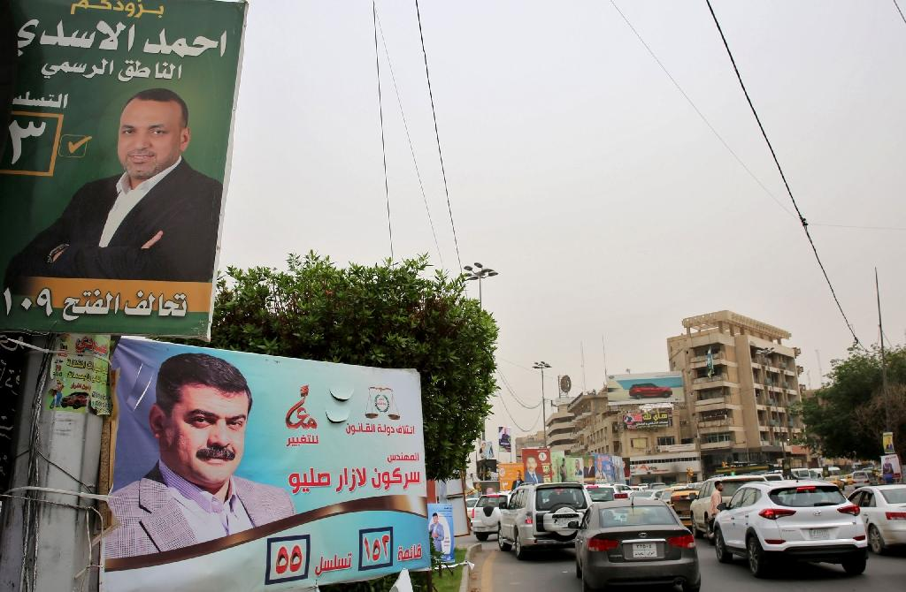 """Ahead of Iraq's upcoming parliamentary elections, an Al-Fath Alliance poster (top) reads: """"Ahmad al-Assadi, the Spokesman"""". Pictured in Baghdad on May 8, 2018 (AFP Photo/SABAH ARAR)"""