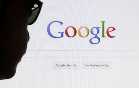 File of a computer user posing in front of a Google search page in this photo illustration taken in Brussels