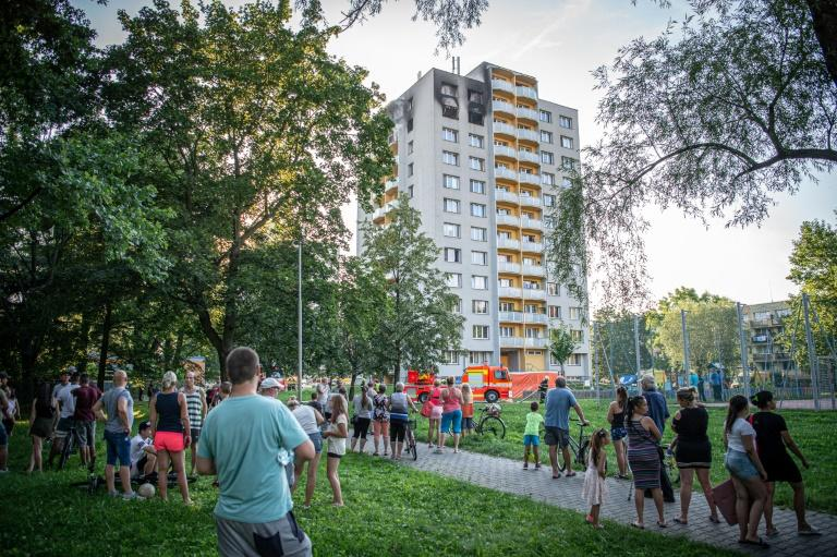 People look on as firefighters work at the scene where a fire broke out in an apartment block in Bohumin, eastern Czech Republic on August 8, 2020, killing eleven people including three children