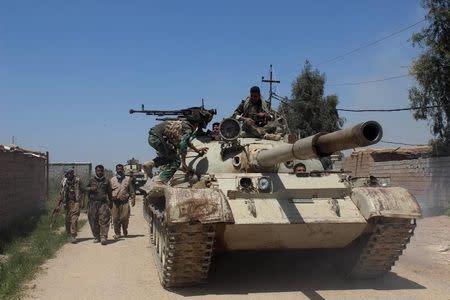 Kurdish peshmerga forces sit on top of a tank on the outskirts of Kirkuk