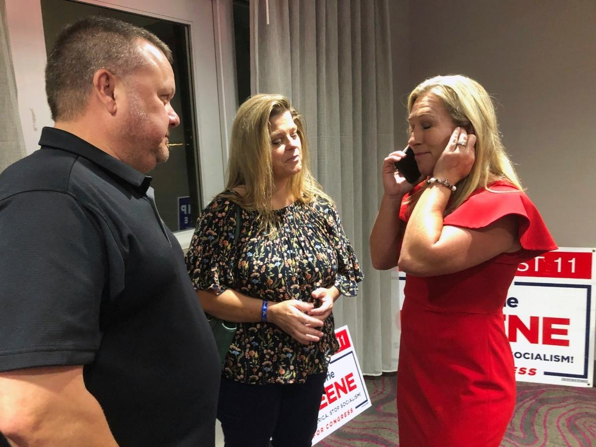 Supporters speak with Marjorie Taylor Greene, the Republican candidate for Georgia's 14th U.S. Congressional district. Her Democratic opponent, Kevin Van Ausdal, dropped out of the race Friday.
