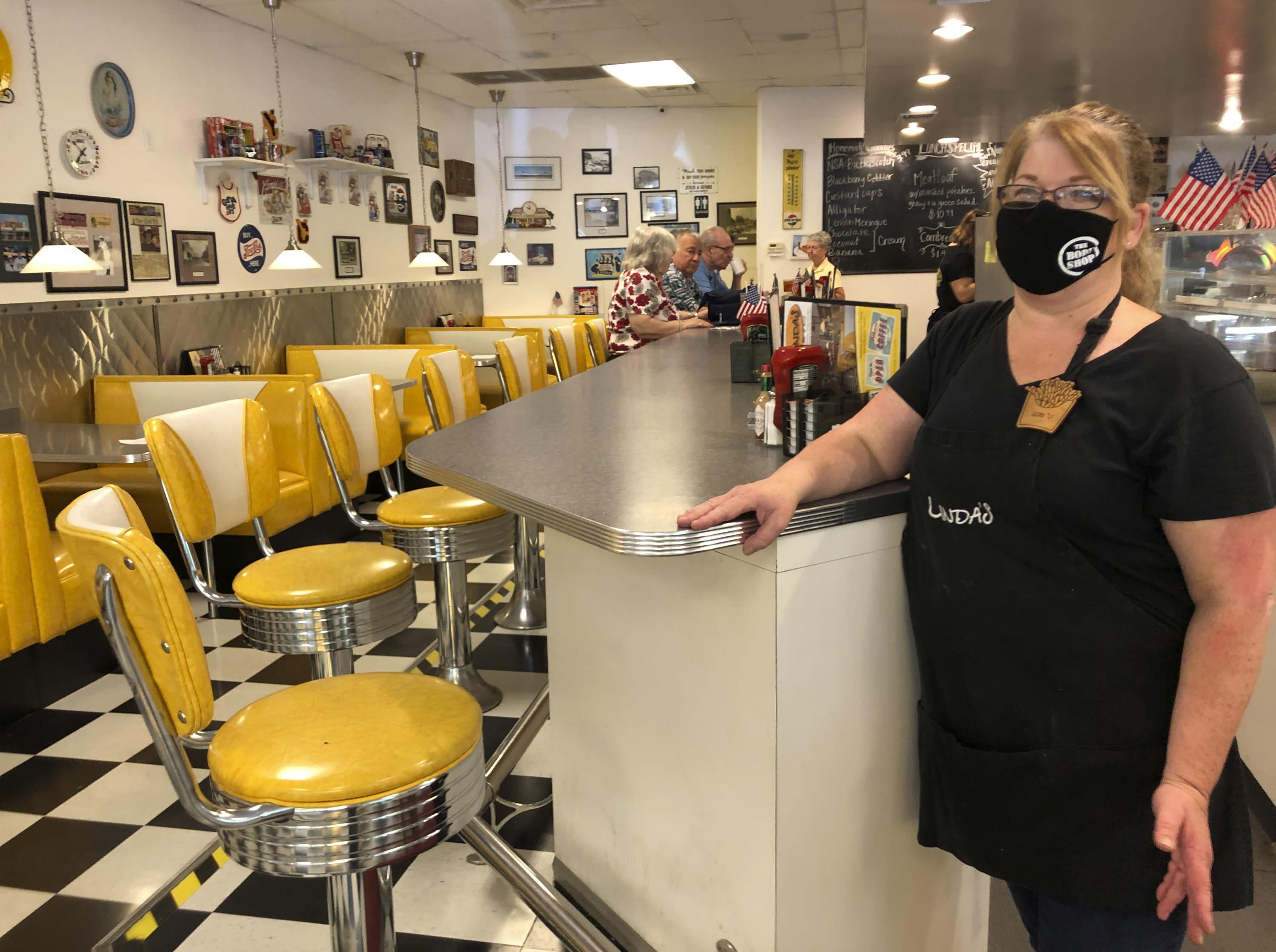 """Restaurant manager Lori Pack stands at the counter of Linda's Soda Bar and Grill in Yuba City, Calif., Thursday, July 9, 2020. Sutter County was one of the first counties to reopen its economy when it defied Gov. Gavin Newsom's stay-at-home order in May to allow restaurants, hair salons, gyms and shopping malls to reopen. But Thursday, the county was added to a state watch list because of its rising number of coronavirus cases and hospitalizations. That will eventually trigger another round of restrictions, forcing bars to close and indoor operations to cease at restaurants and other public places for three weeks. Pack says the restaurant tried takeout-only service for three weeks earlier this year during the coronavirus pandemic. But she said it was """"just not sustainable."""" (AP Photo/Adam Beam)"""
