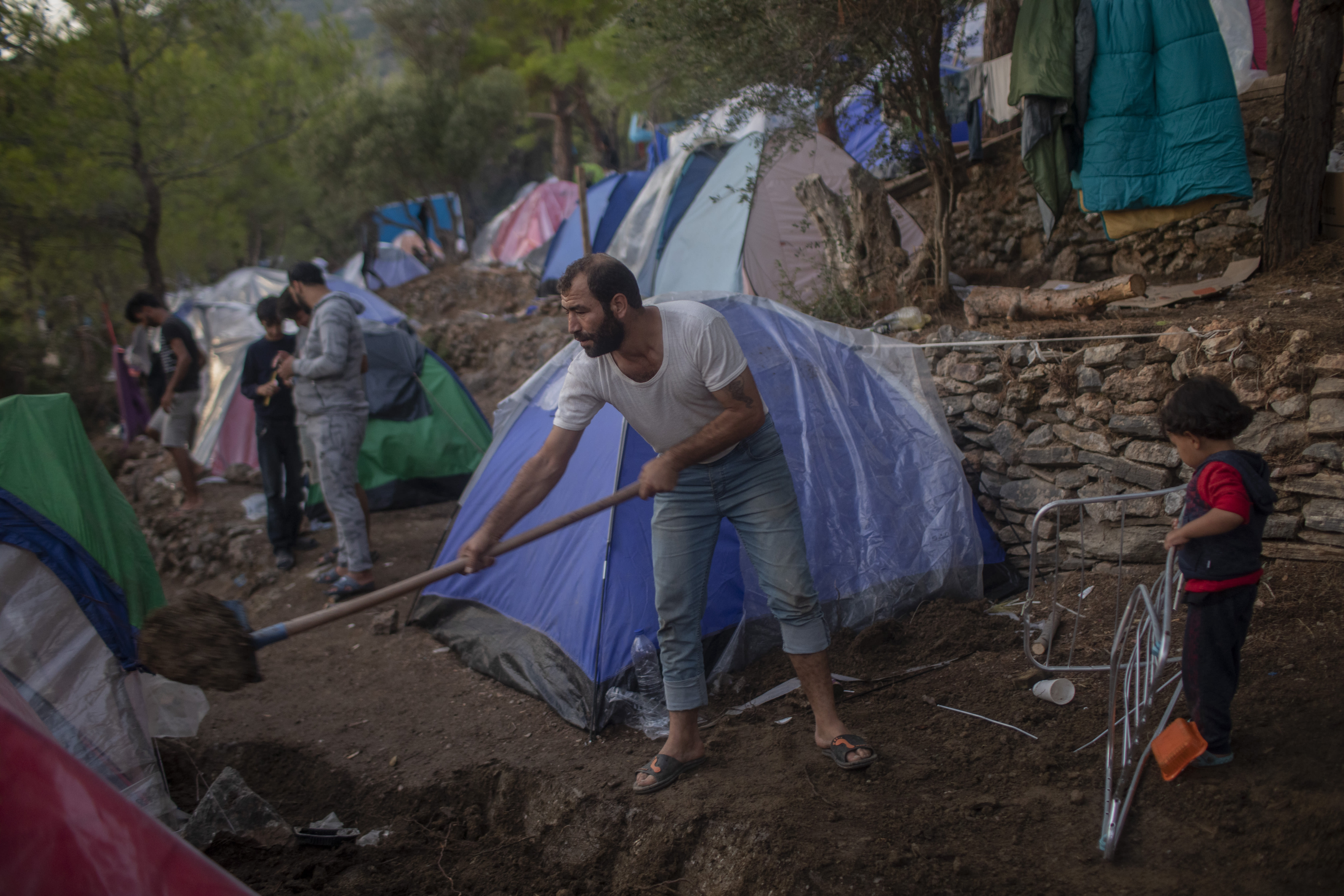 FILE - In this Sept. 25, 2019 file photo, a Syrian man shovels dirt next to his tent near the refugee and migrant camp at the Greek island of Samos island. The head of the U.N. food agency warned of starvation and another wave of mass migration from Syria to Europe unless donors countries step up financial assistance to the war-ravaged country. (AP Photo/ Petros Giannakouris, File)