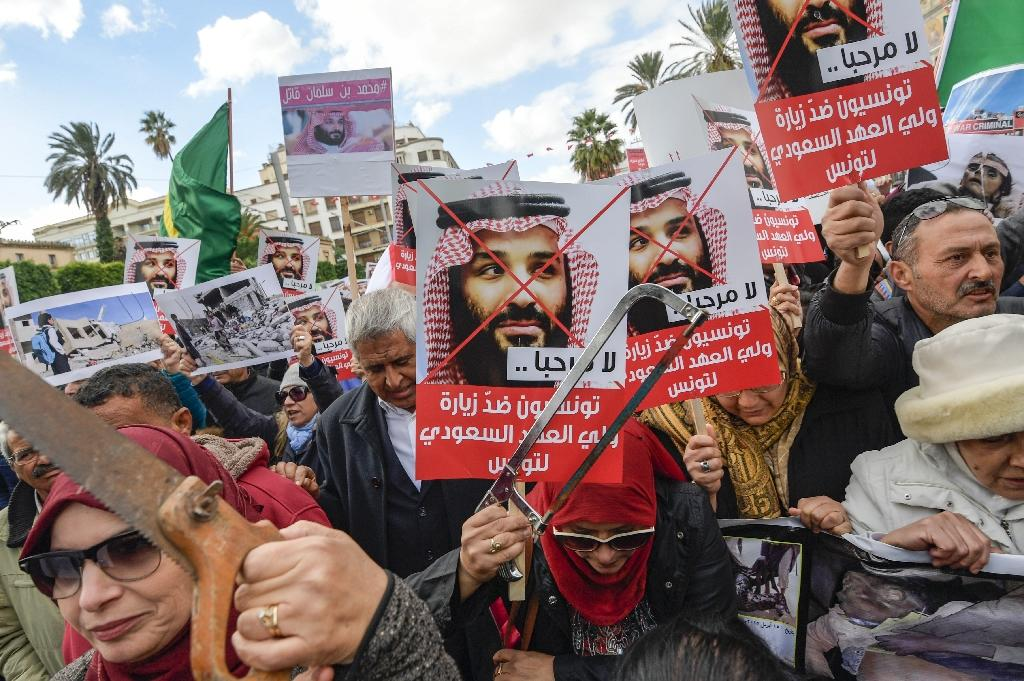 """Tunisian women hold up saws and signs saying in Arabic, """"No welcome, Tunisians against the visit of the Saudi Crown Prince to Tunisia"""", during an anti-Saudi Crown Prince protest in Tunis on November 27, 2018"""