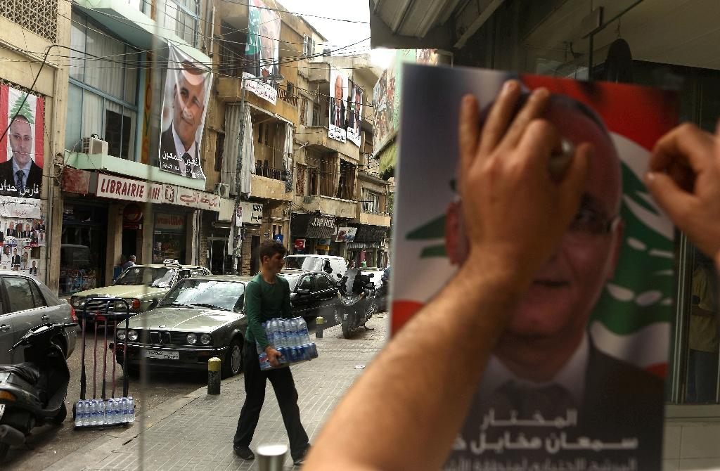 A Lebanese man puts up a poster of a candidate in the Beirut municipal elections (AFP Photo/Patrick Baz)