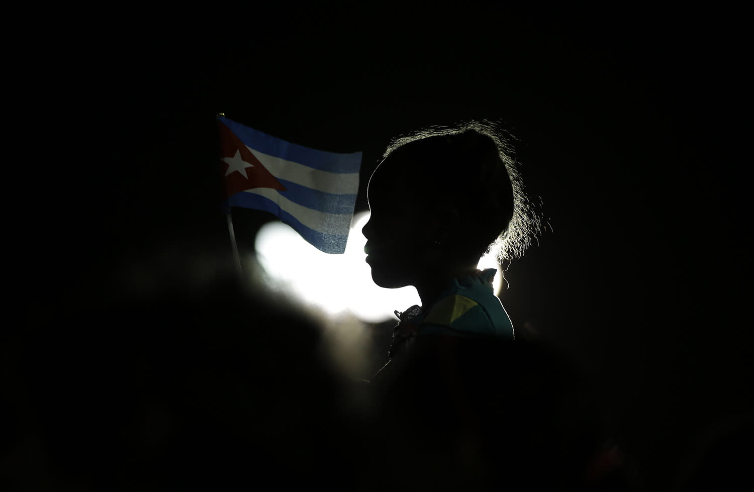 <p>A girl holds a Cuban flag during a rally honoring late Fidel Castro at Antonio Maceo plaza, the day his ashes arrived to Santiago, Cuba, Dec. 3, 2016. (Photo: Natacha Pisarenko/AP) </p>