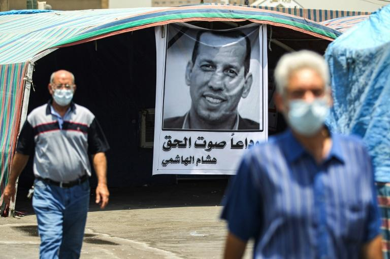 Men clad in masks due to the COVDI-19 coronavirus pandemic walk past a mourning tent bearing the poster of slain Iraqi jihadism expert Hisham al-Hashemi in Baghdad