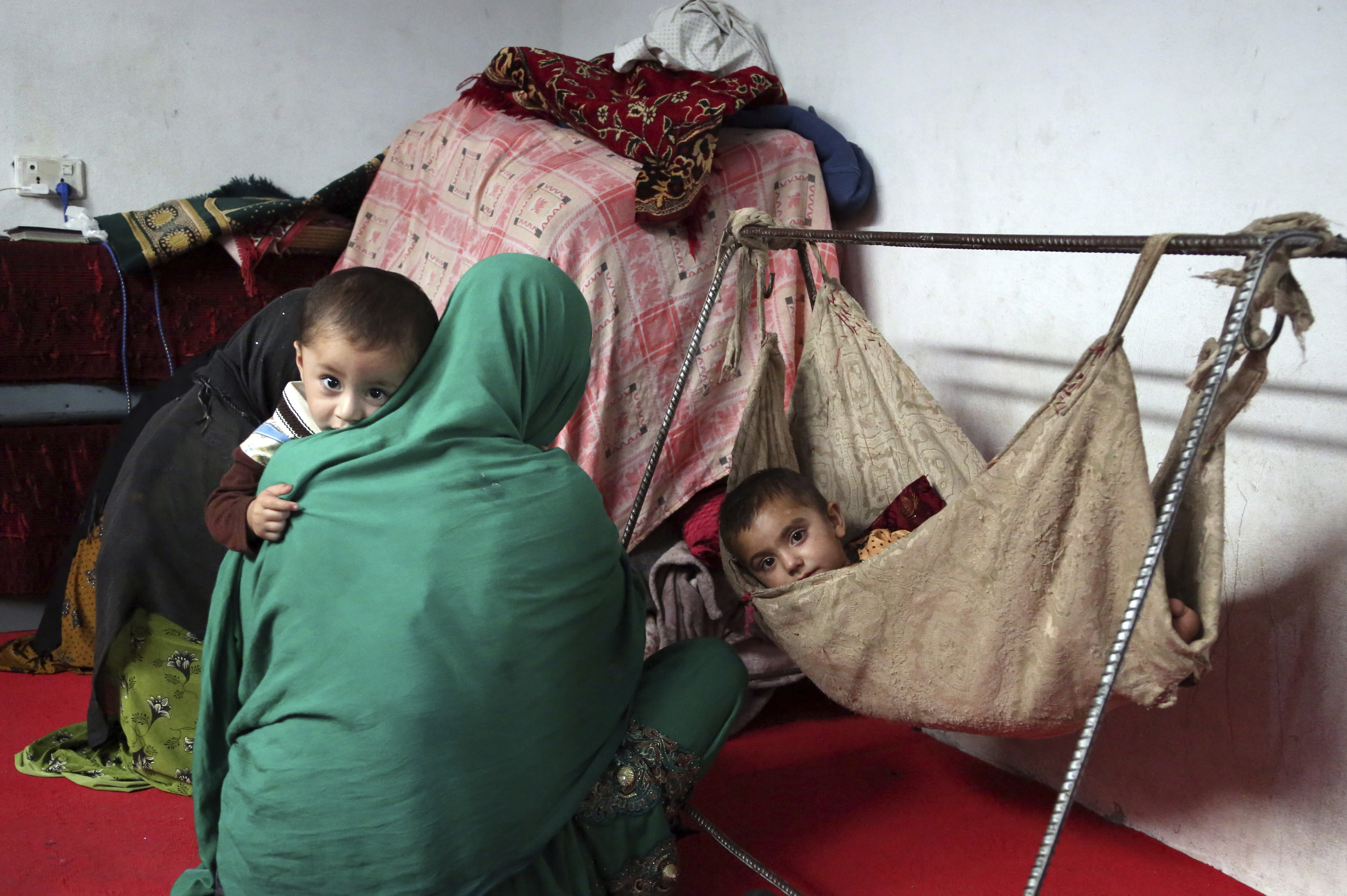 In this Thursday, May 30, 2019 photo, members of Farmanullah Shirzad's family who fled their village in Nangarhar province in late April as Islamic State group fighters swept through the area, are seen at their temporary home in the city of Jalalabad east of Kabul, Afghanistan. The Islamic State group has lost its caliphate in Syria and Iraq, but in the forbidding mountains of northeastern Afghanistan the group is expanding its footprint, recruiting new fighters and plotting attacks in the United States and other Western countries. (AP Photo/Rahmat Gul)