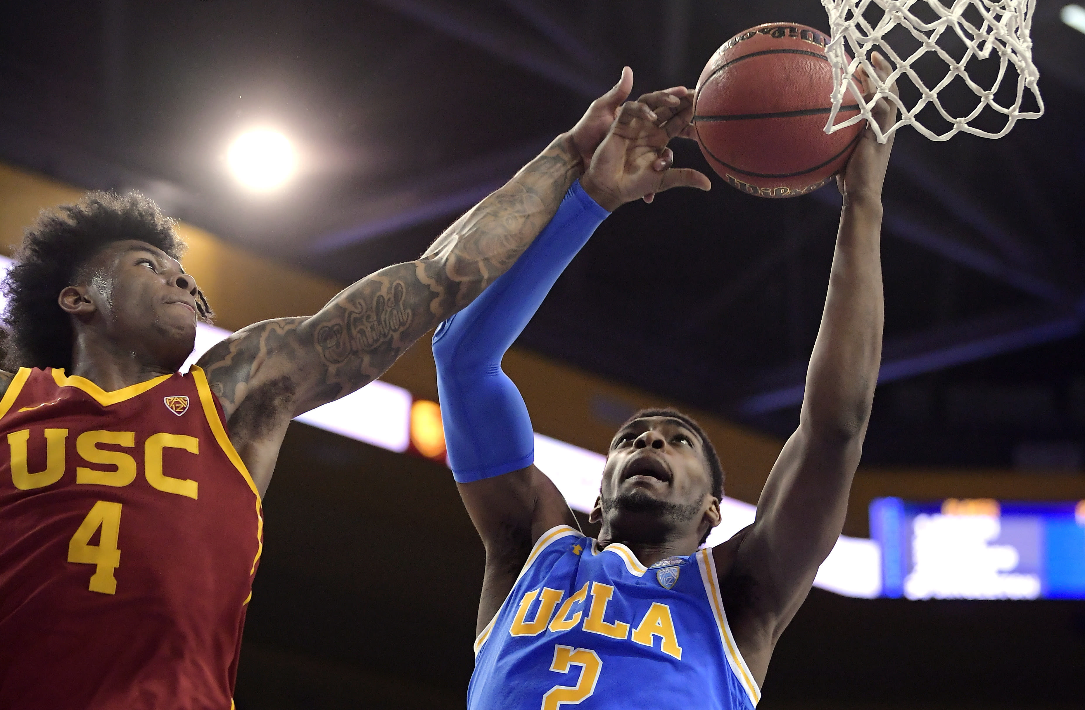 FILE - In this Feb. 28, 2019, file photo, UCLA forward Cody Riley, right, grabs a rebound away from Southern California guard Kevin Porter Jr. during the first half of an NCAA college basketball game in Los Angeles. The NCAA's Board of Governors is urging Gov. Gavin Newsom not to sign a California bill that would allow college athletes to receive money for their names, likenesses or images. In a six-paragraph letter to Newsom, the board said the bill would give California schools an unfair recruiting advantage. As a result, the letter says, the NCAA would declare those schools ineligible for its events. (AP Photo/Mark J. Terrill, File)