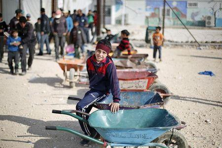 Syrian children wait to carry customers' goods using wheelbarrows, in front of the Tazweed Center at the Al-Zaatari refugee camp in the Jordanian city of Mafraq