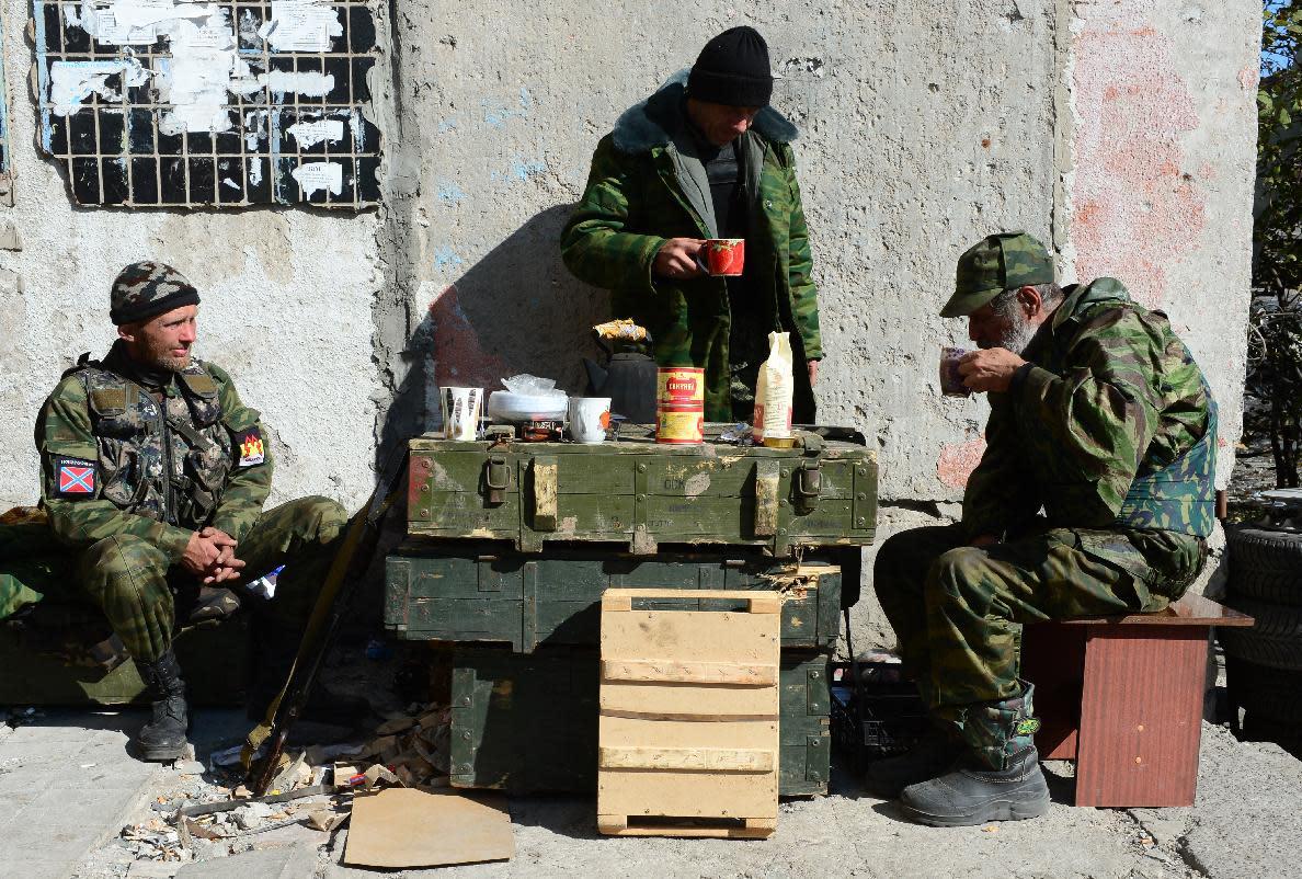 Pro-Russian separatist soldiers take a break near Donetsk's Sergey Prokofiev international airport where fighting continues between Ukrainian army forces and pro-Russian separatist soldiers, on October 9, 2014 (AFP Photo/John MacDougall)