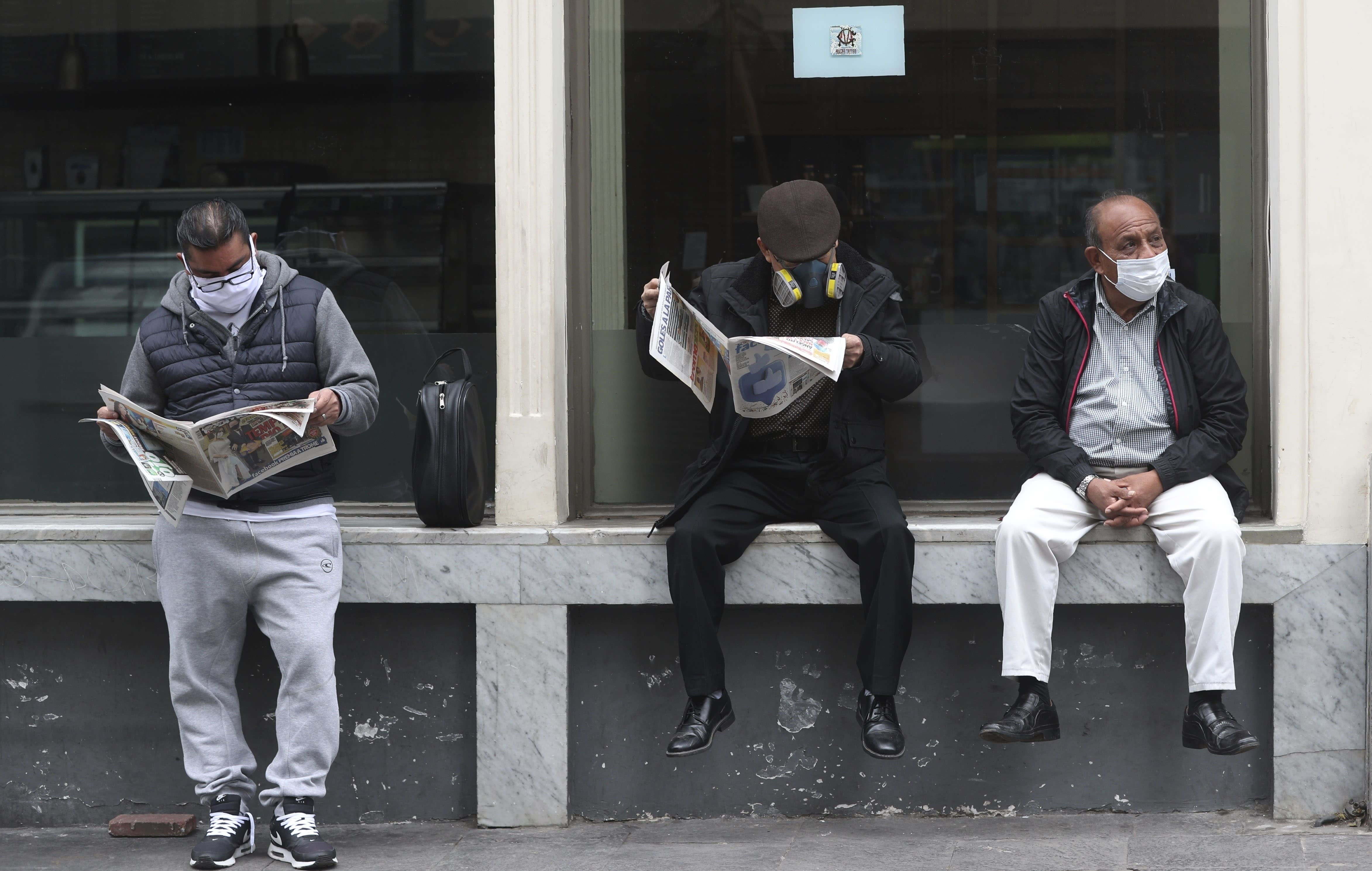 People wearing masks to curb the spread of the new coronavirus wait for businesses to open in downtown Lima, Peru, Wednesday, July 1, 2020. (AP Photo/Martin Mejia)