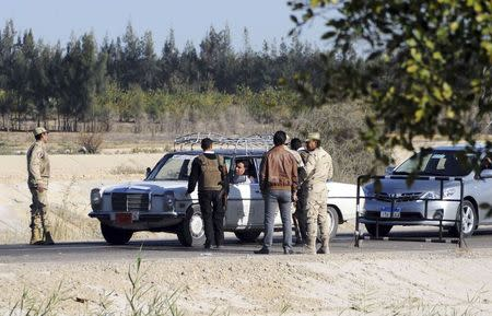Egyptian security personnel check cars at a checkpoint near the site, where separate attacks on security forces in North Sinai on Thursday killed 30 people, in Arish, North Sinai