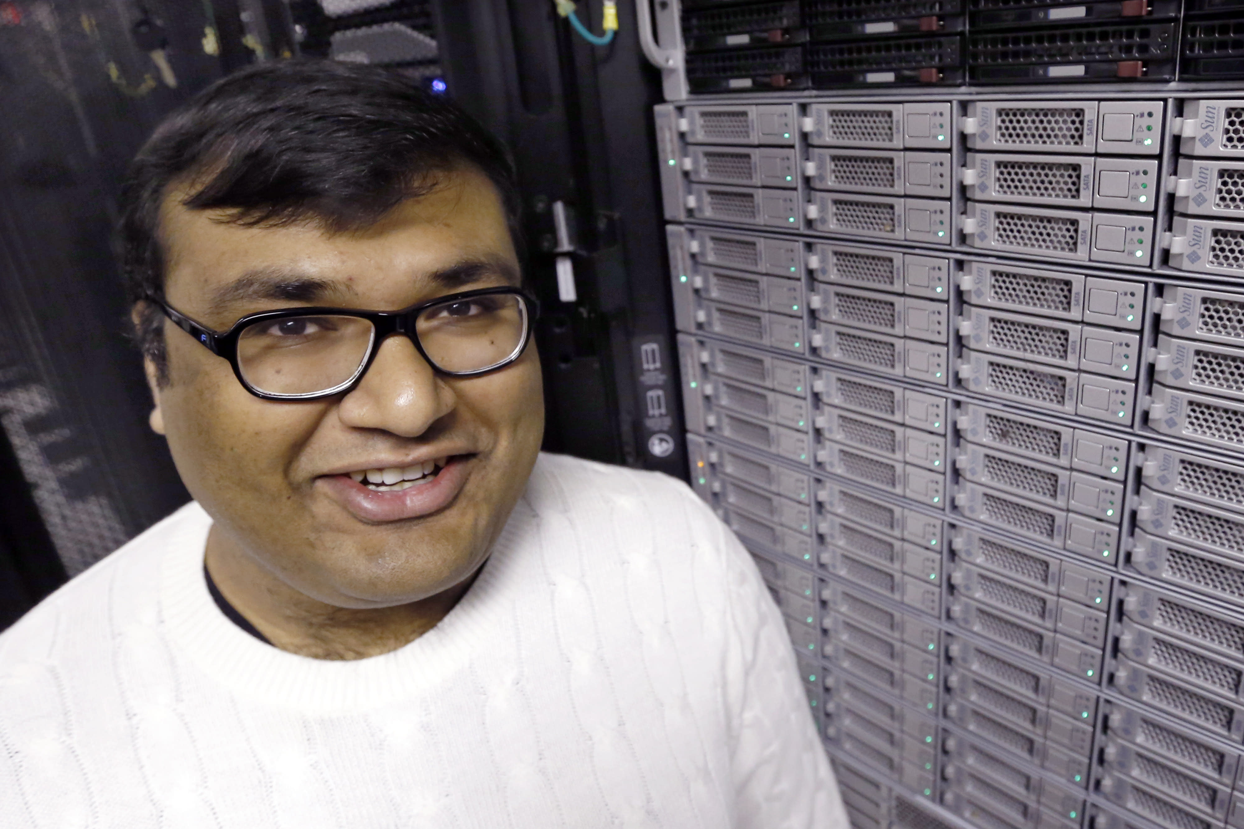 In this Thursday, Nov. 21, 2013 photo, Abhinav Gupta stands near one of the computer clusters used in his research at one of the computer server areas on campus at Carnegie Mellon University in Pittsburgh. The school is letting hundreds of computers run constantly to scan millions of images off the Internet, and have the computers make connections on their own. The plan is to let the system run forever. (AP Photo/Keith Srakocic)