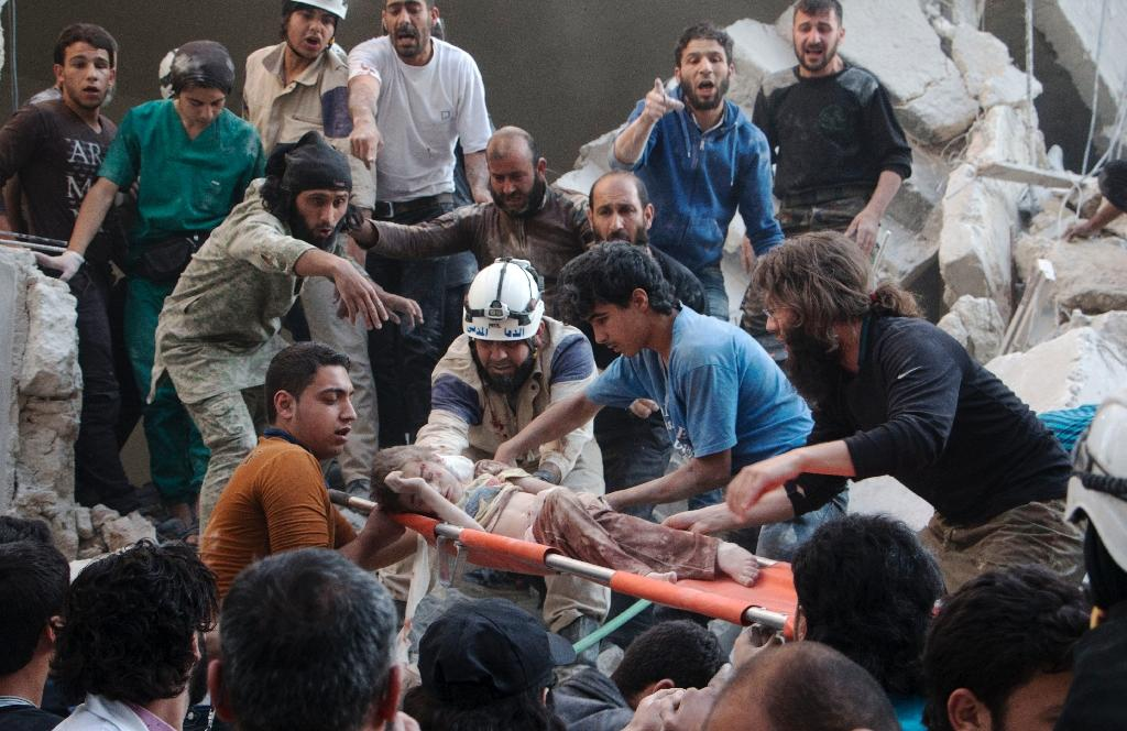 Syrian rescue workers and citizens carry a child on a stretcher from a building following a reported barrel bomb attack by government forces at the Al-Firdaws neighbourhood of Aleppo on May 30, 2015 (AFP Photo/Karam Al-Masri)