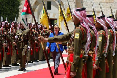 German Chancellor Angela Merkel reviews an honor guard upon her arrival at the Royal Palace in Amman, Jordan June 21, 2018. REUTERS/Muhammad Hamed