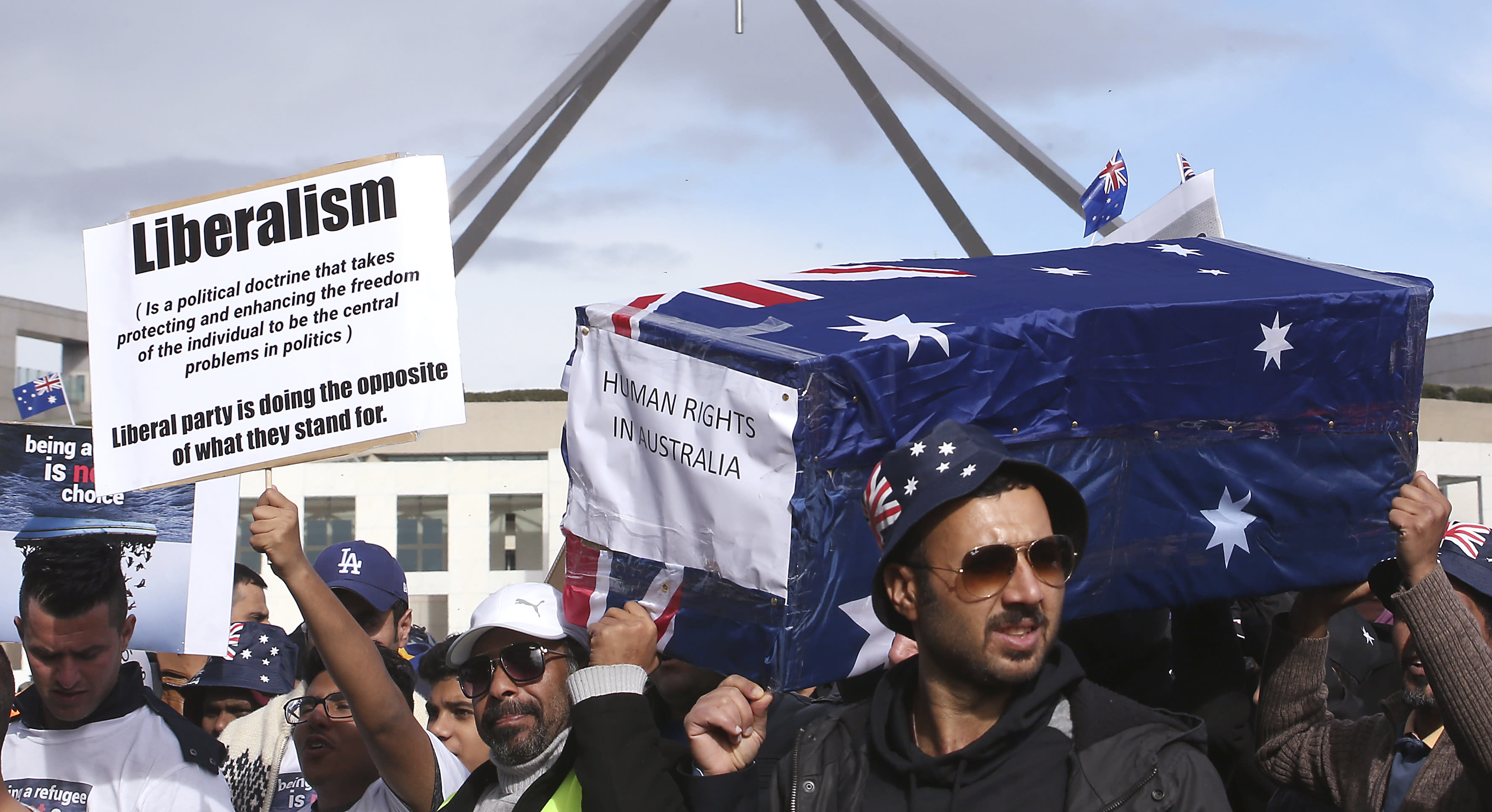 Protestors hold up a placard and a symbolic coffin during a refugee protest at Parliament House in Canberra, Australia, Monday, July 29, 2019. Hundreds of protesters are rallying outside Parliament House highlighting the uncertain futures of many refugees since Australia replaced permanent protection visas with temporary visas. (AP Photo/Rod McGuirk)