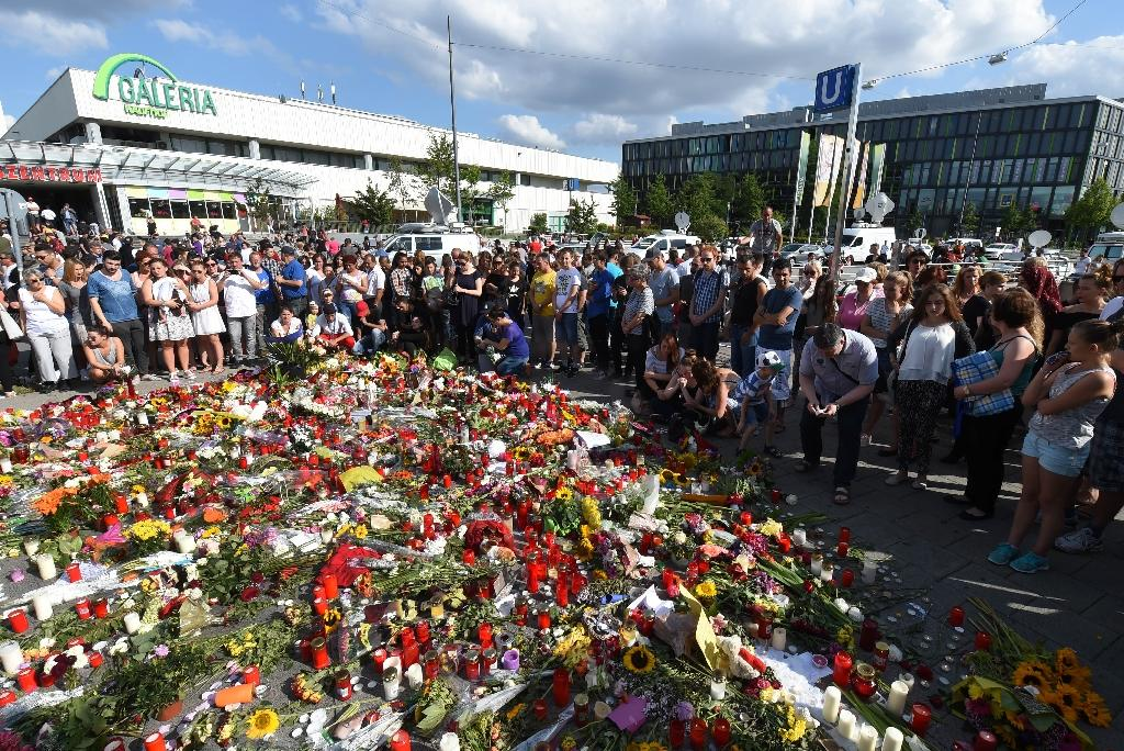 People mourn at a memorial of candles and flowers on July 24, 2016 in front of the Olympia Einkaufszentrum shopping centre in Munich, southern Germany, where an 18-year-old German-Iranian student run amok (AFP Photo/Christof Stache)