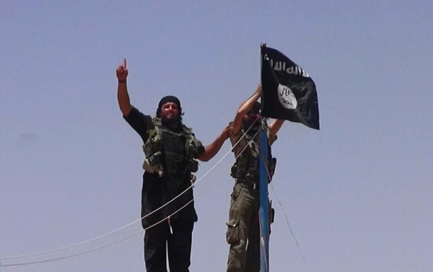 Militants hang the Islamic State flag at a fort on the Syrian-Iraqi border in June, 2014. Two men have been charged in Australia with sending fighters to Syria (AFP Photo/)
