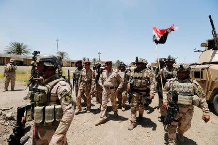 Baghdad Operations Command's head Lieutenant-General Abdul Ameer al-Shammari (C) walks in the town of Garma, Iraq, May 26, 2016. REUTERS/Thaier Al-Sudani