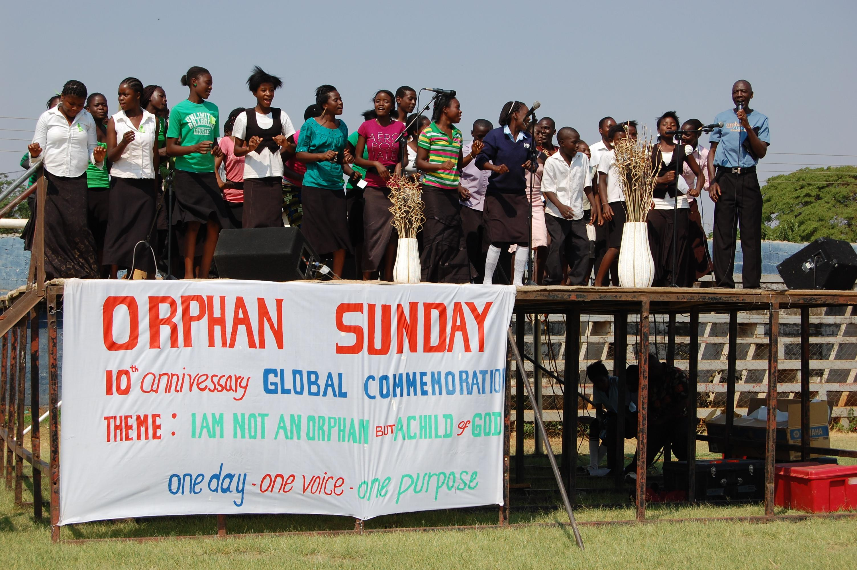 """In this 2012 photo provided by the Christian Alliance for Orphans, a pastor, right, speaks on stage accompanied by orphaned children from the Lusaka region to celebrate """"Orphan Sunday"""" in Lusaka, Zambia. Organizers of Orphan Sunday, which started on a large scale in 2009, say 2013's event will be bigger than ever, unfolding in every state and many foreign countries. Yet it comes at a time with the number of international adoptions dwindling and the adoption movement encountering criticisms so forceful that some of its own leaders are paying heed. (AP Photo/Christian Alliance for Orphans)"""